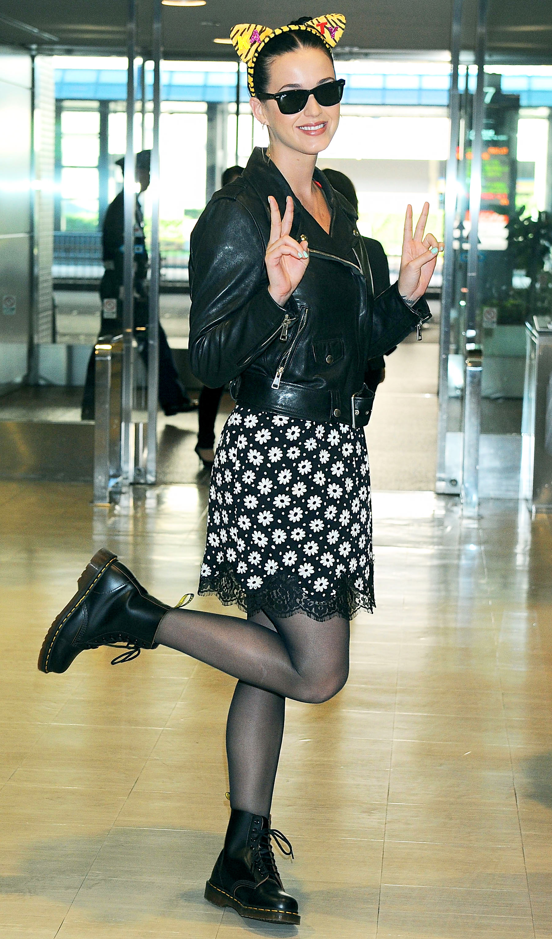 Arriving in Japan in cat ears, a moto jacket, and a black-and-white floral printed dress.
