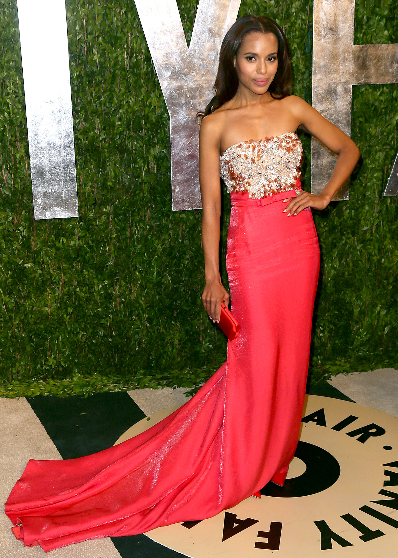 Washington stunned in a dark pink Miu Miu gown with beaded embellishments and red heels while attending the 2013 Vanity Fair Oscar Party at the Sunset Tower Hotel.