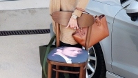 Jane Fonda carries a chair with Ryan Gosling's face on it