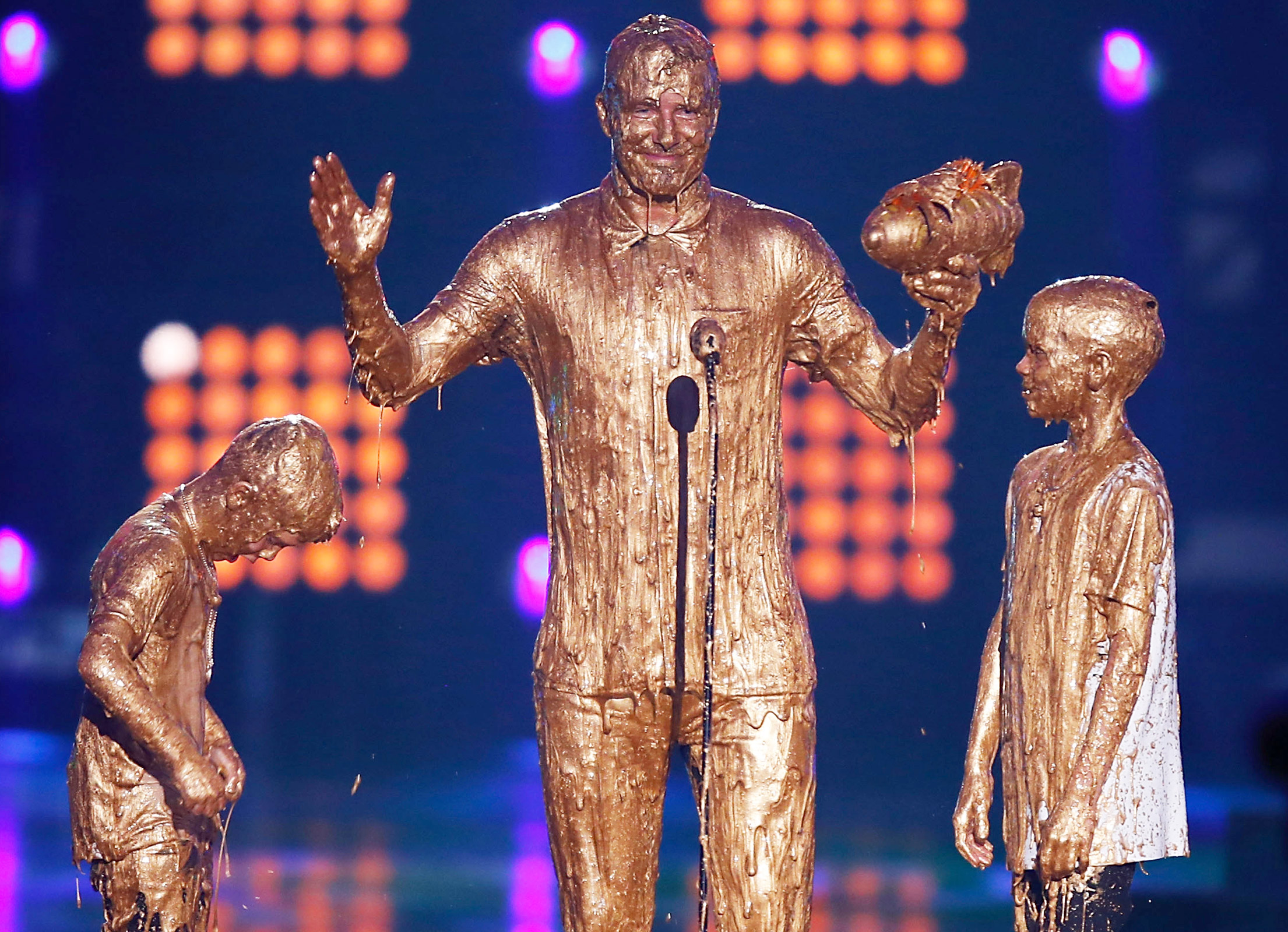 From posh to splosh! The former soccer pro received an award from his young sons Romeo and Cruz at the inaugural Nickelodeon Kids' Choice Sports Awards in L.A., but the Beckham family's special moment was cut short when they unexpectedly got smothered onstage by golden slime.