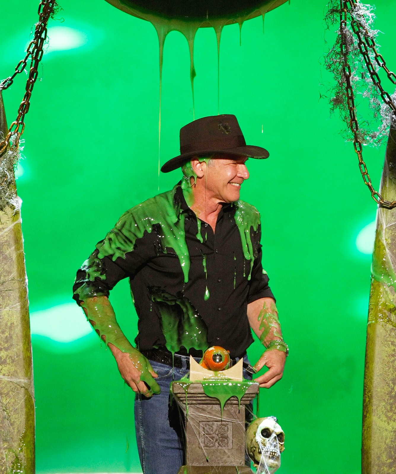"Shia LaBeouf (not pictured) tricked his Indiana Jones and the Kingdom of the Crystal Skull costar into donning his character's costume and retrieving the winner's name from an orb inside the Pauley Pavilion in Westwood, Calif., on March 29, 2008. ""I'll handle this,"" Ford said just before a goblet of green goo flipped upside down and drenched the actor."
