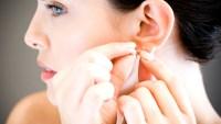 Woman putting on earrings