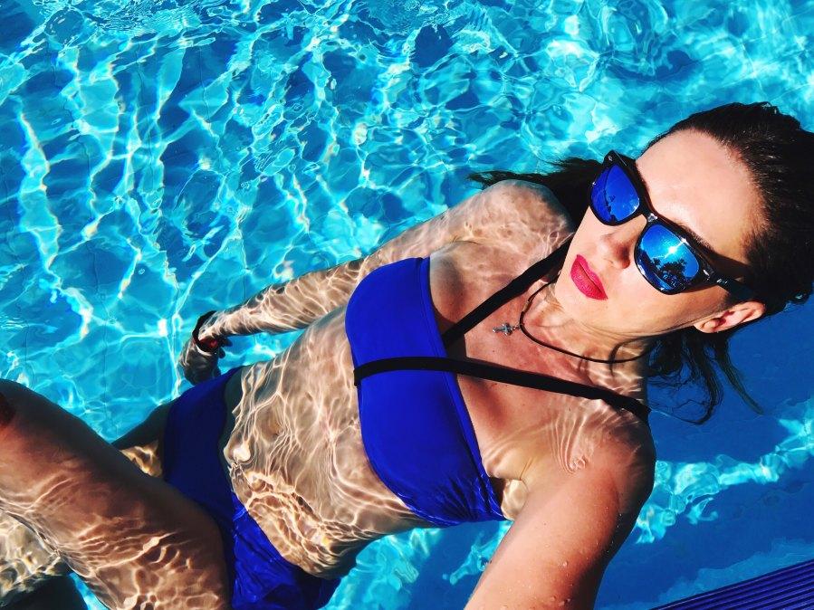 Woman in pool with bright lipstick and bikini