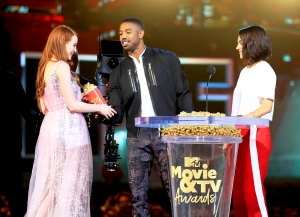Madelaine Petsch and Mila Kunis present Michael B. Jordan with the Best Villain award for 'Black Panther', onstage during the 2018 MTV Movie And TV Awards at Barker Hangar on June 16, 2018 in Santa Monica, California.