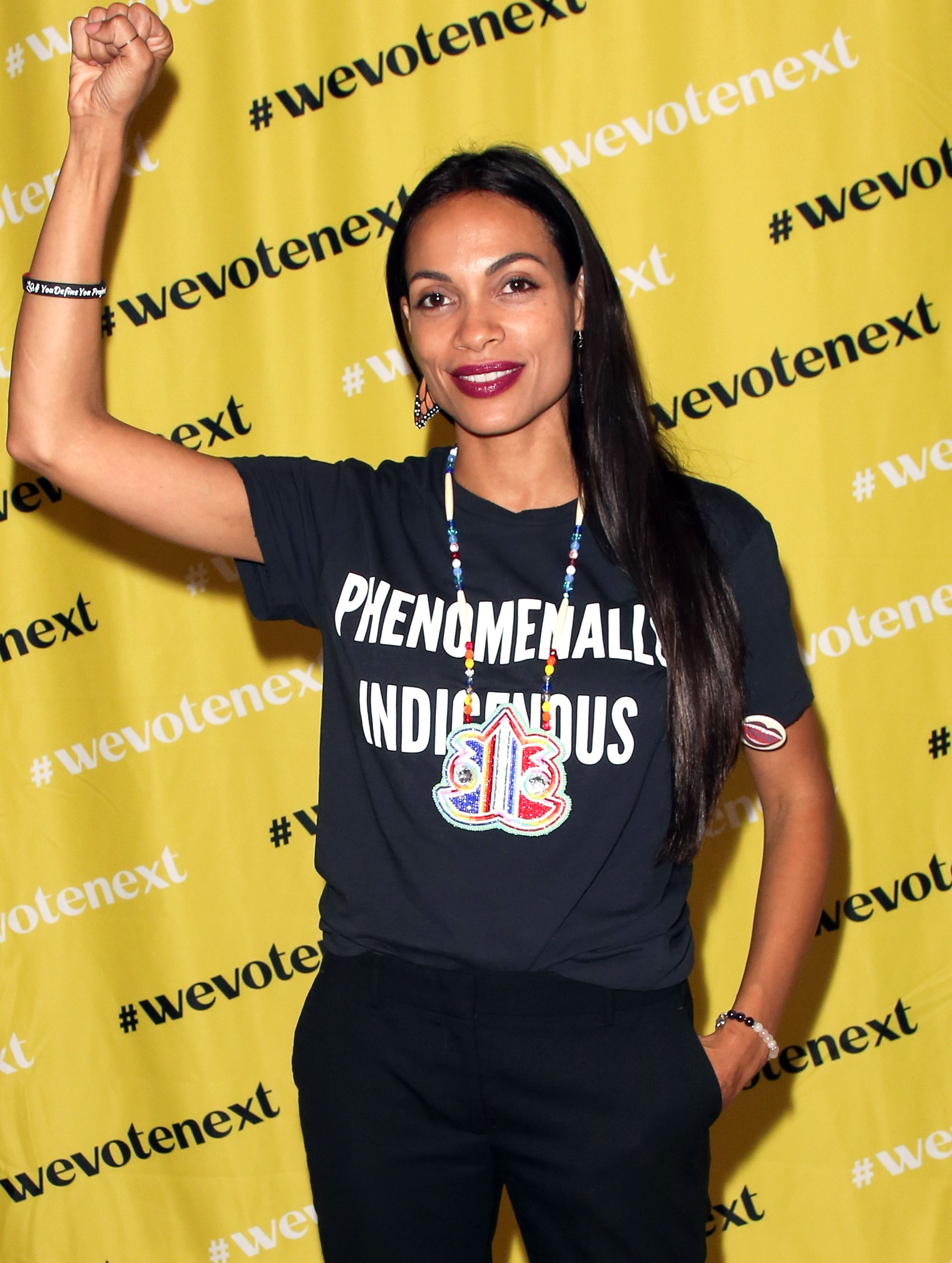 """Rosario-Dawson - With Indigenous Peoples' Day just a week away, Dawson showed her support over the weekend. The actress attended the We Vote Next Summit event presented by Eigteen X 18 in L.A. wearing a tee that featured big bold text that reads """"Phenomenally Indigenous"""" on September 29, 2018."""