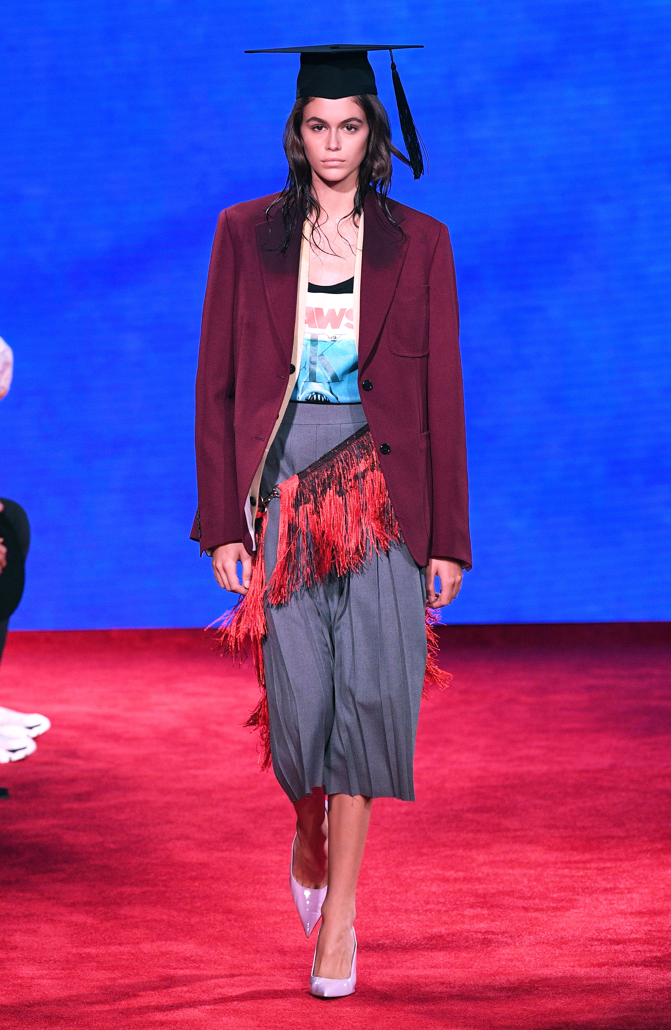 Kaia Gerber - Gerber walked the Calvin Klein show during New York Fashion Week in a Jaws graphic tee underneath a burgundy jacket, a pleated skirt with a red fringe belt and a black graduation cap.