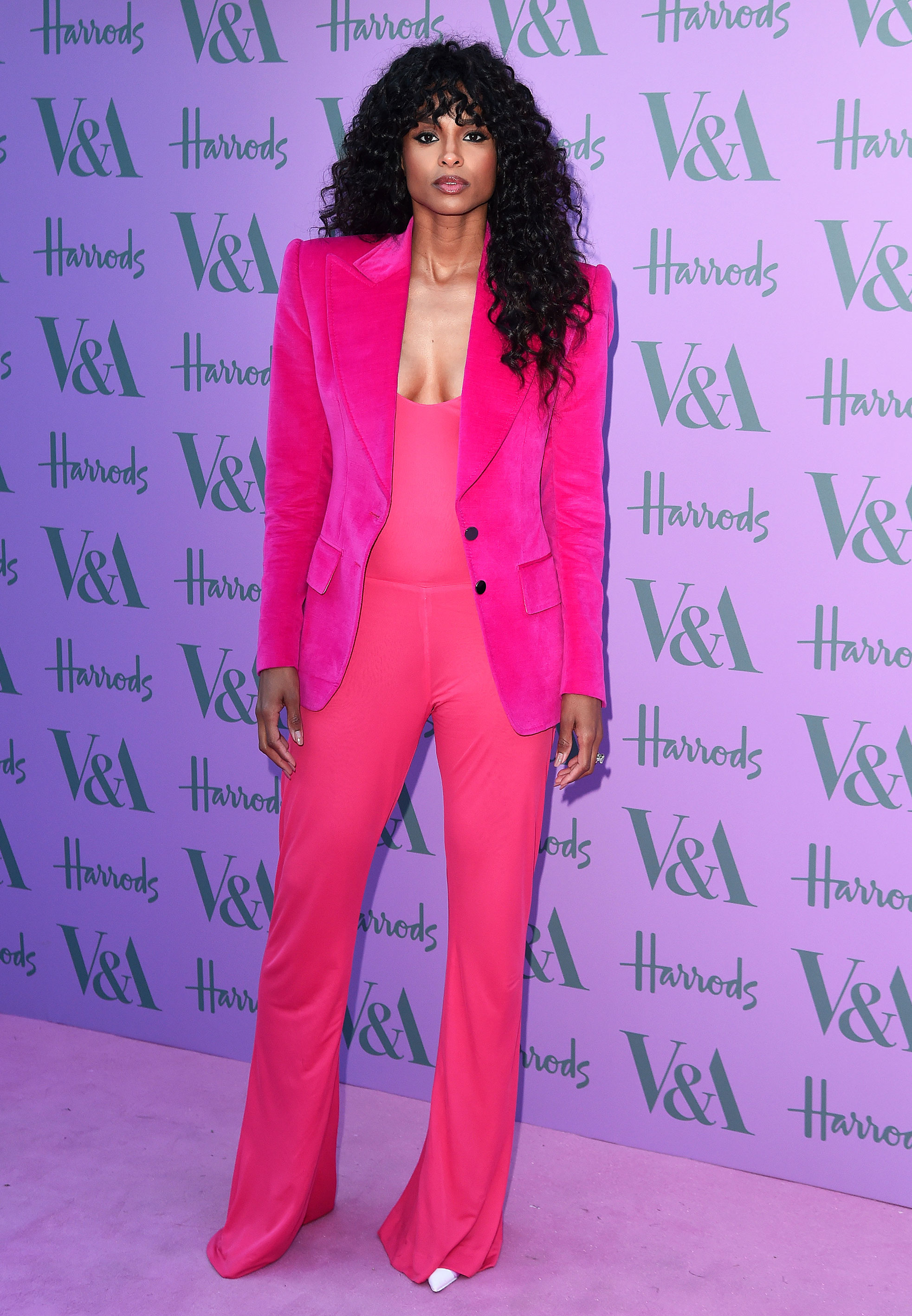 Ciara - Wearing a hot pink Tom Ford velvet jacket, jumpsuit and satin kicks.