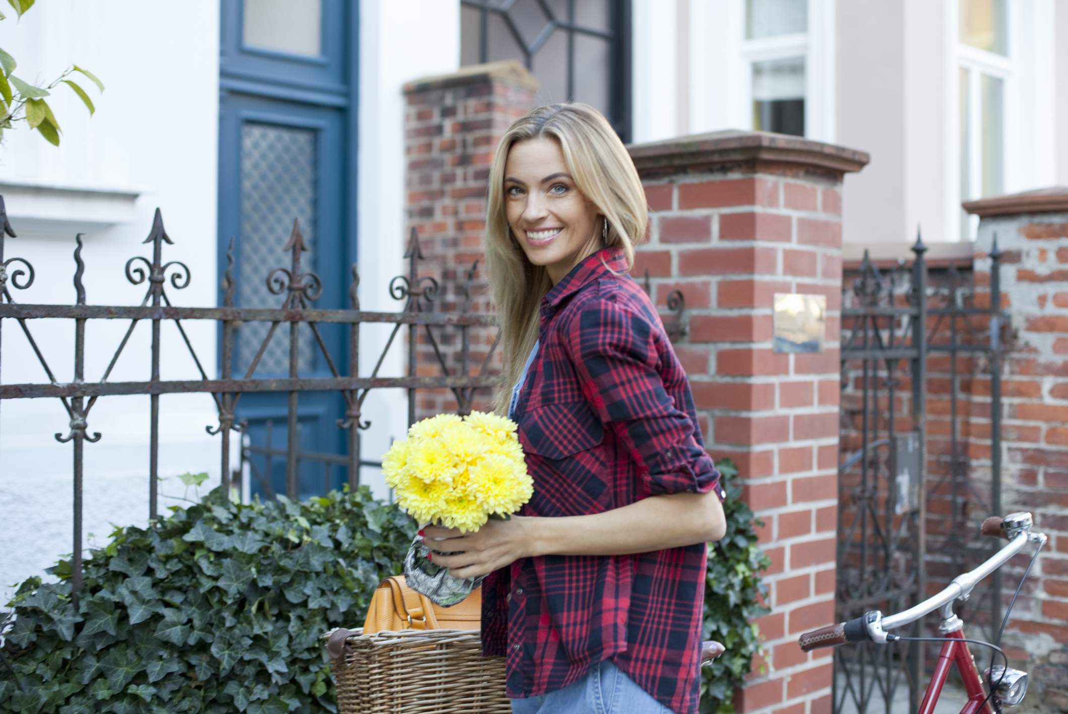 smiling woman with bicycle and fresh flowers