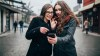 Two female friends using phone downtown