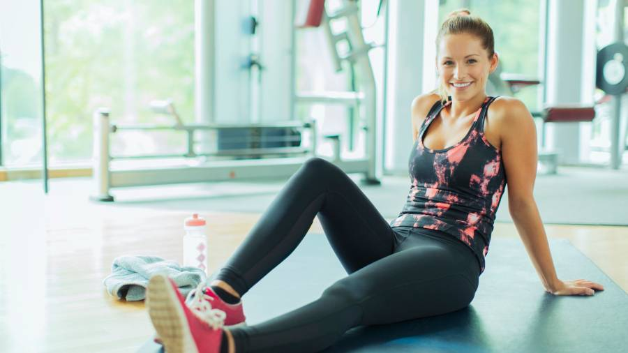 Portrait smiling woman resting on mat in gym