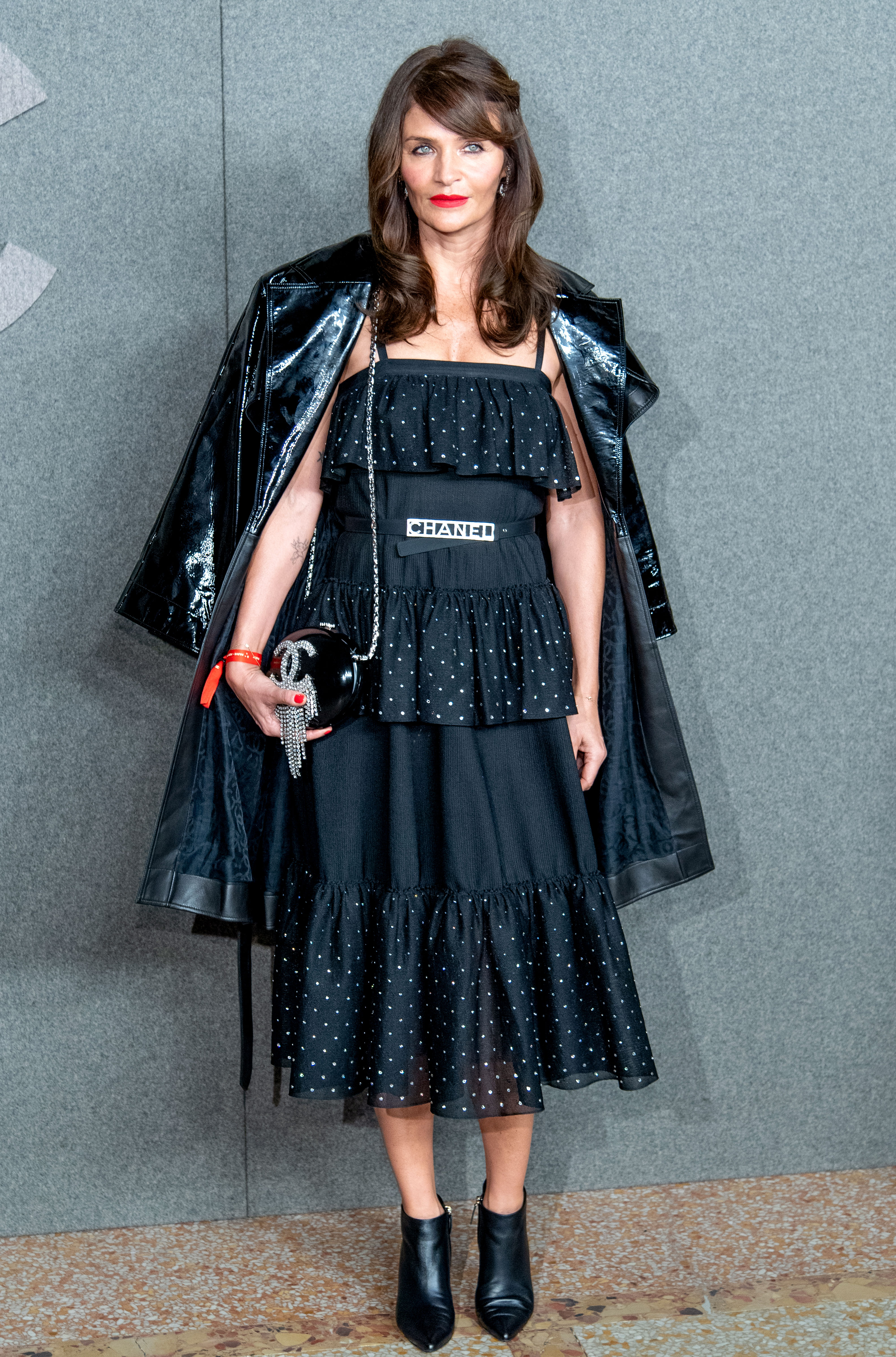 Helena-Christensen- - The model was layered up in a tiered black dress and patent trench.