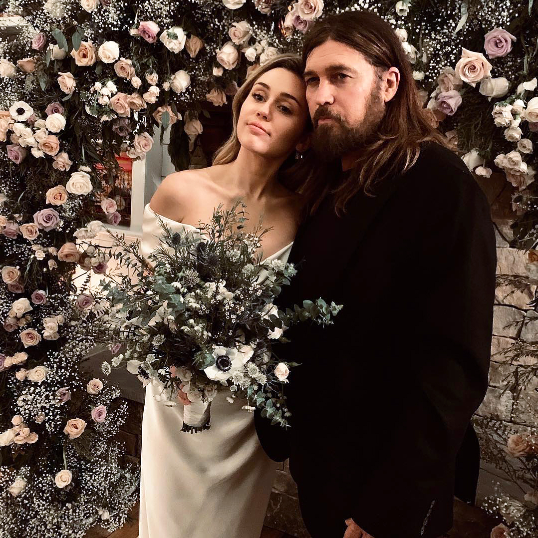 Miley Cyrus Liam Hemsworths Secret Wedding - Billy Ray Cyrus and Miley posed for a sweet snap in front of a flower wall.