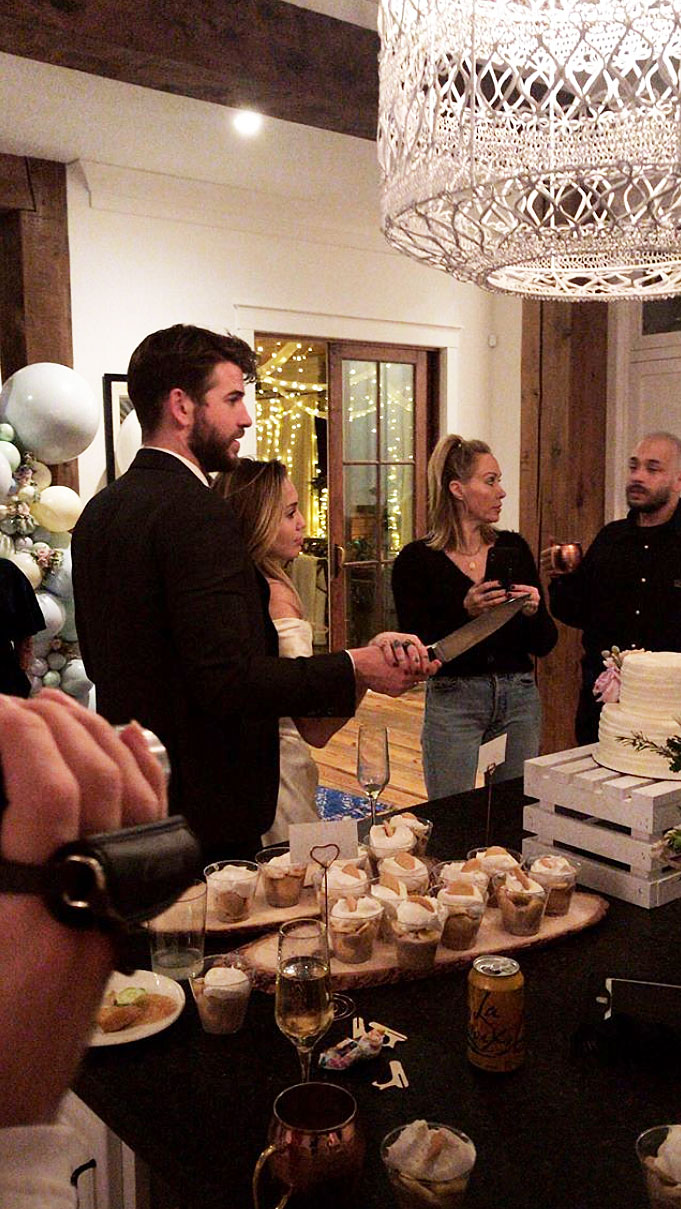 Miley Cyrus Liam Hemsworths Secret Wedding - The lovebirds held on to each other as they cut their wedding cake.