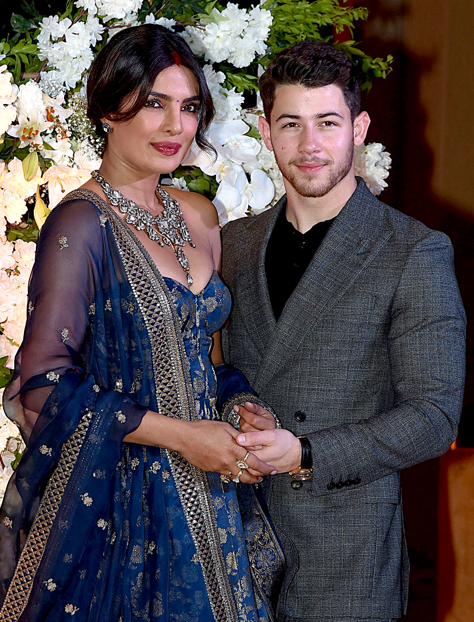 Nick-Jonas-and-Priyanka-Chopra-Mumbai-Wedding-Reception - While Chopra stunned in a royal blue and gold dress and rocked a giant diamond necklace, Jonas looked handsome in a gray suit.