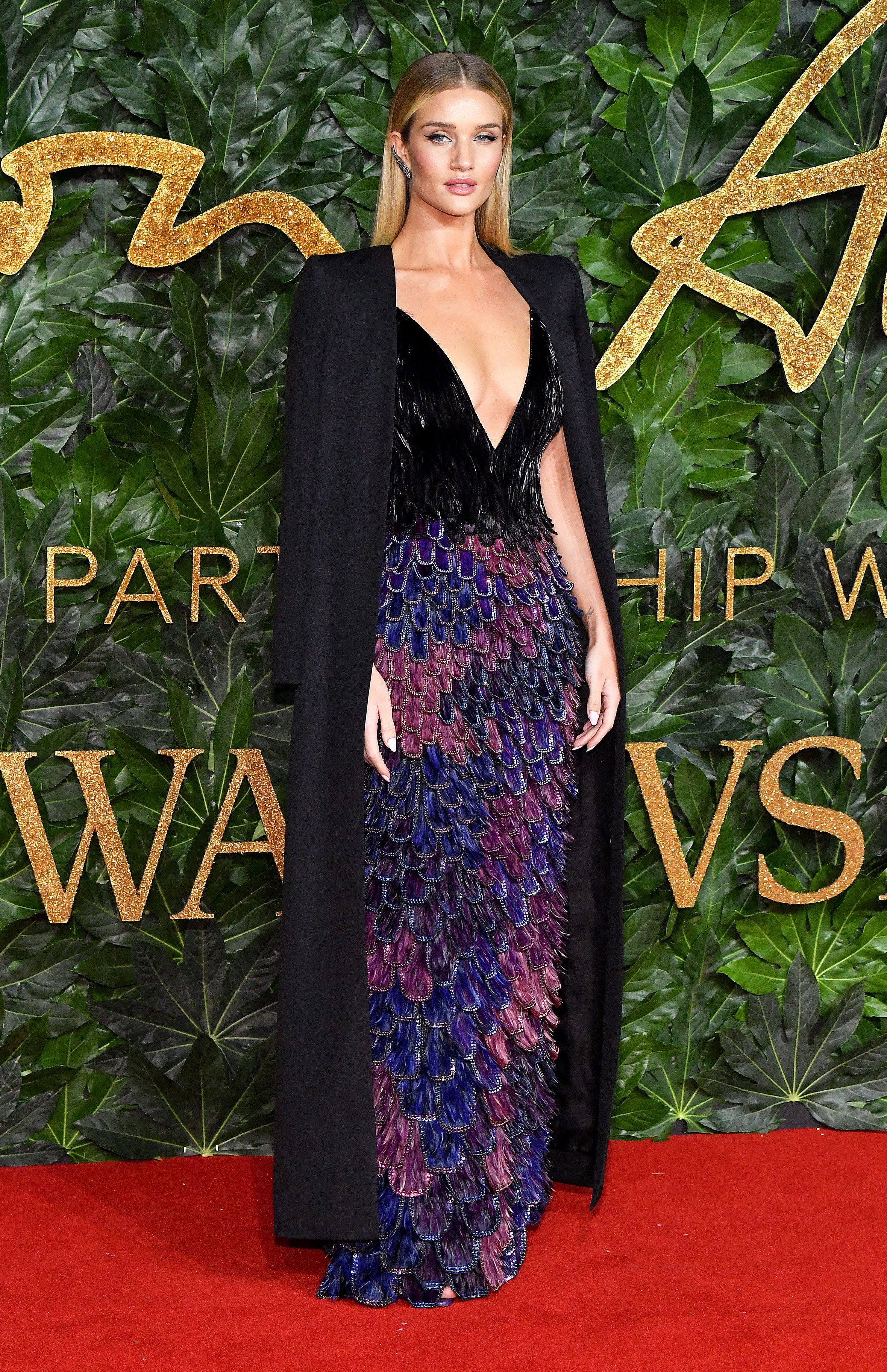 Rosie-Huntington-Whiteley - Mirroring Duchess Meghan, the model was statuesque in a tiered velvet Givenchy gown and dramatic cape.