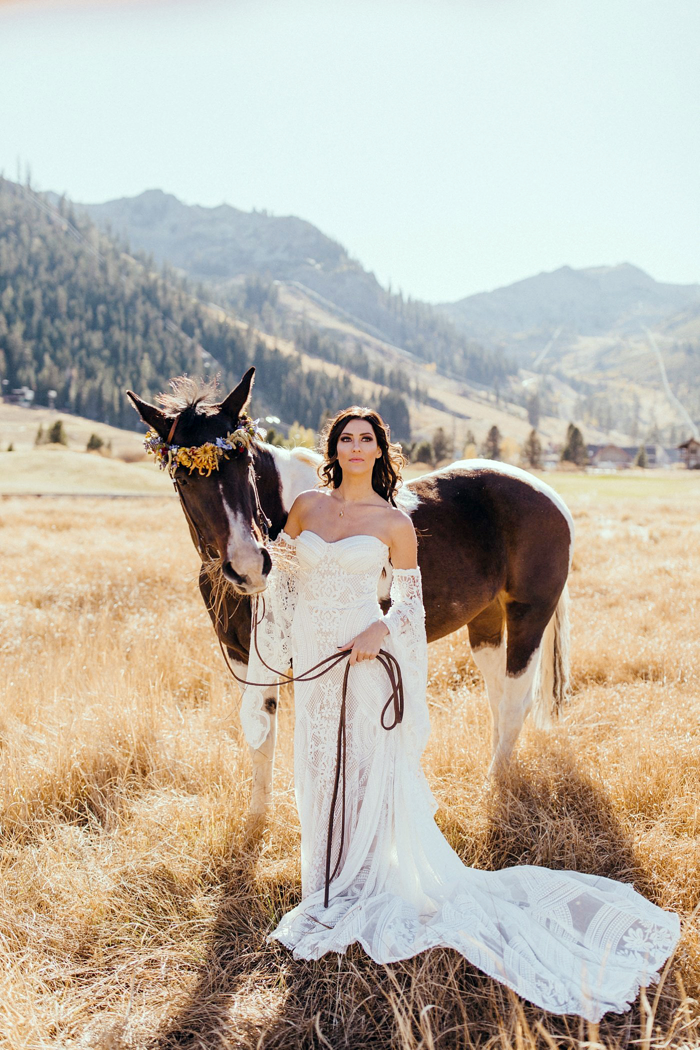 Becca Kufrin Garrett Yrigoyen Pre-Wedding Shoot - Kufrin stunned in an off-the-shoulder lace Rue De Seine gown from Swoon Bridal as she stood alongside a horse adorned with flowers.
