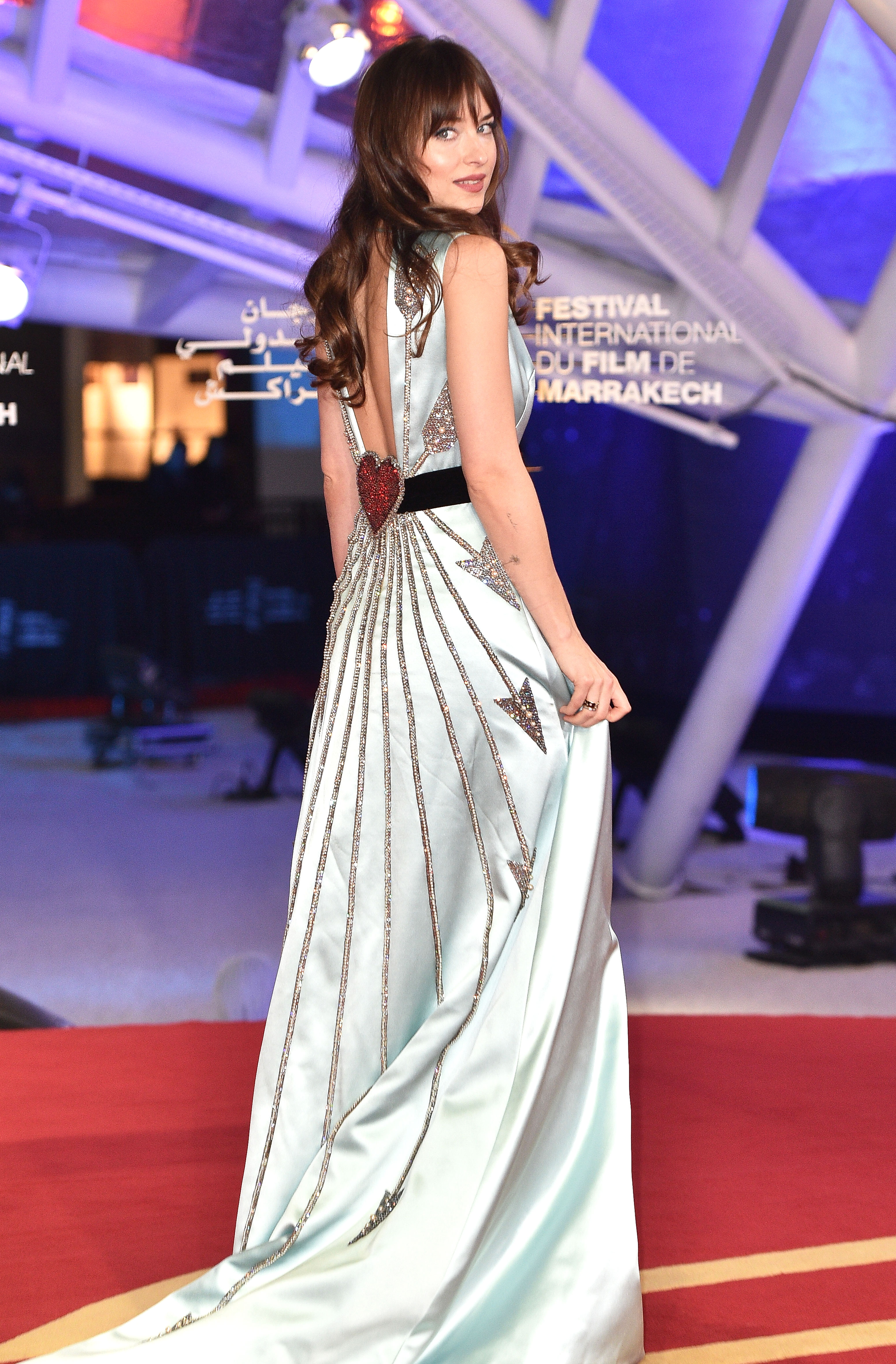 dakota-johnson - Talk about a grand finale! At the closing ceremony on Saturday, December 8, the brunette beauty had a real-life Cinderella moment in a custom pale blue Gucci gown that featured an embellished heart and arrow motif on the back.
