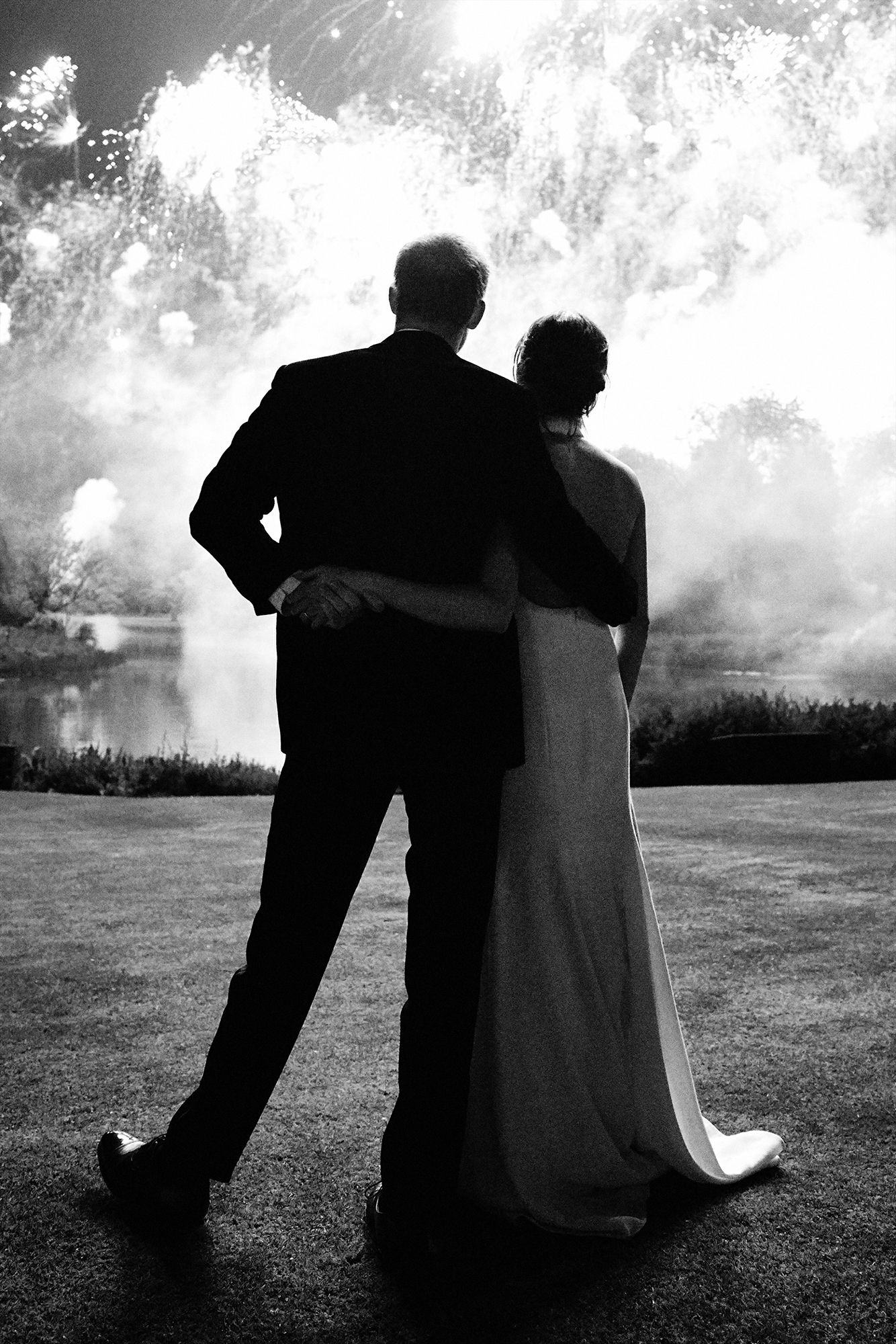 prince-william-kate-middleton-holiday-card-2018 - Harry and Meghan kicked off their first holiday season as a married couple by releasing an unseen photo of their nuptials in December 2018. In the sweet snap, the couple are watching fireworks from their wedding reception at Frogmore House.