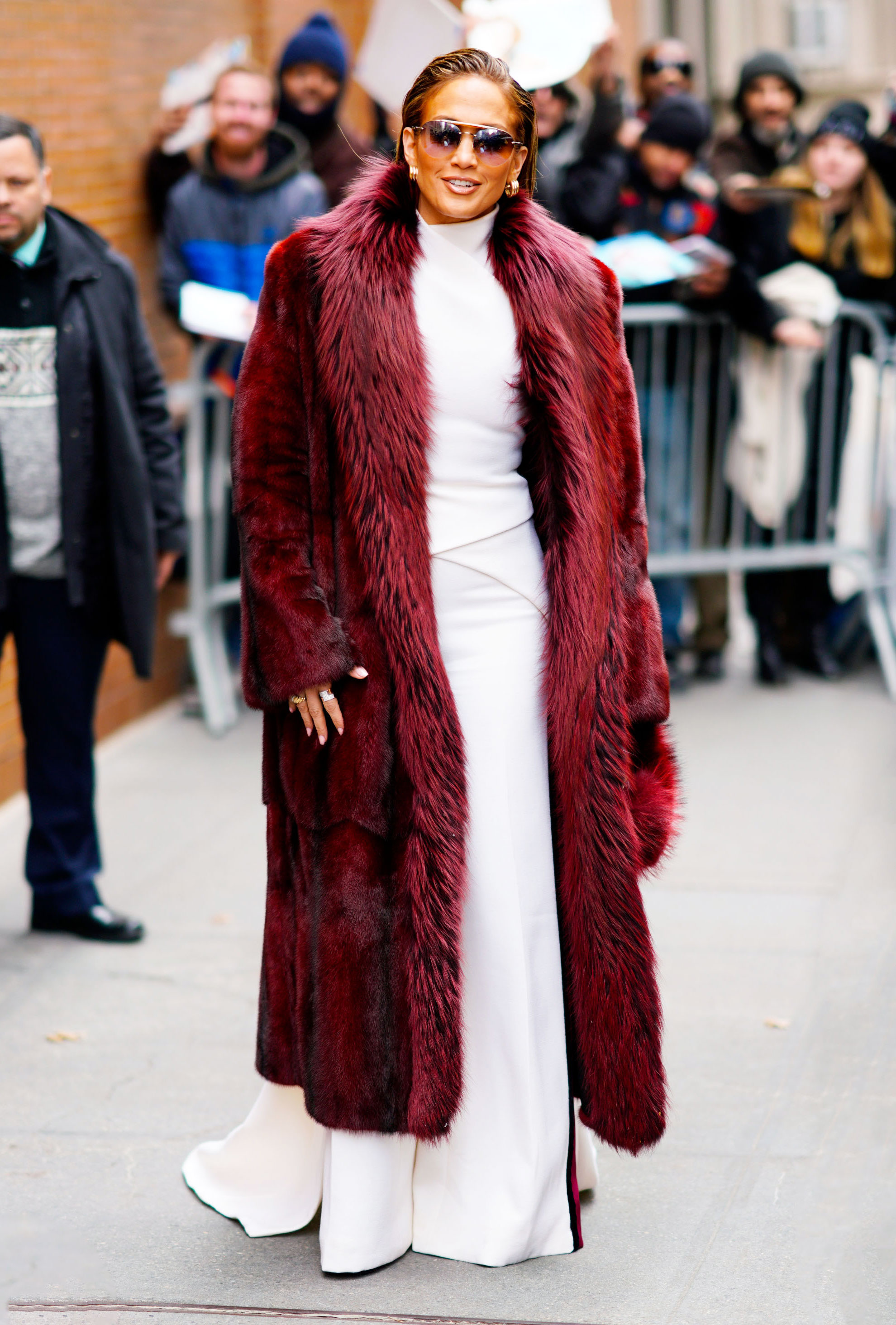 jennifer-lopez-Second-Act-press-coat - Arriving at The View on Wednesday, December 12, the Second Act star topped off her winter white look with a burgundy fur coat and matching clutch.