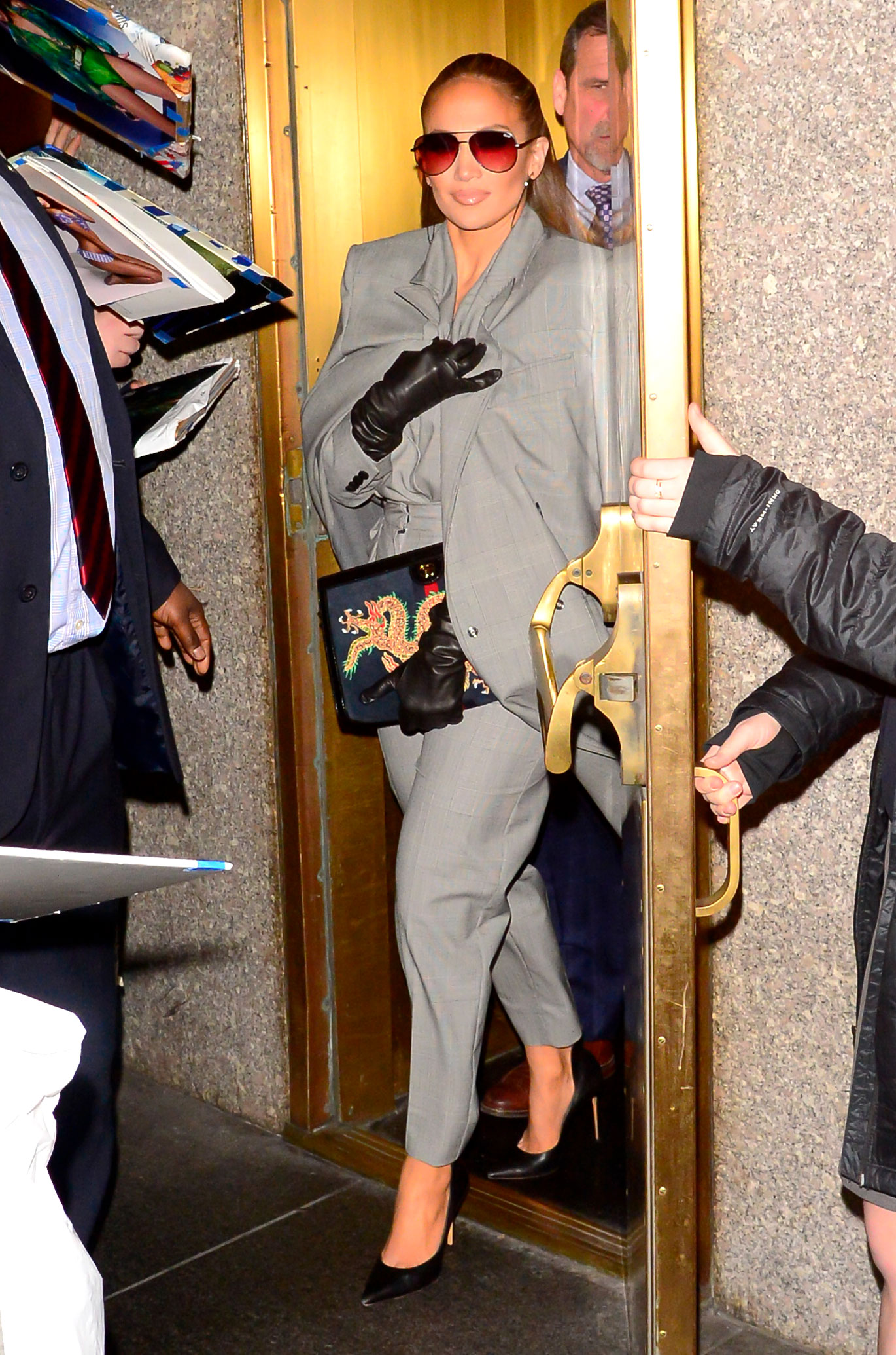 jennifer-lopez-Second-Act-press-gray-suit - A true boss lady, Lopez was seen outside the NBC studios on Tuesday, December 11, in Max Mara suiting that she accessorized with a Gucci clutch and Quay frames.