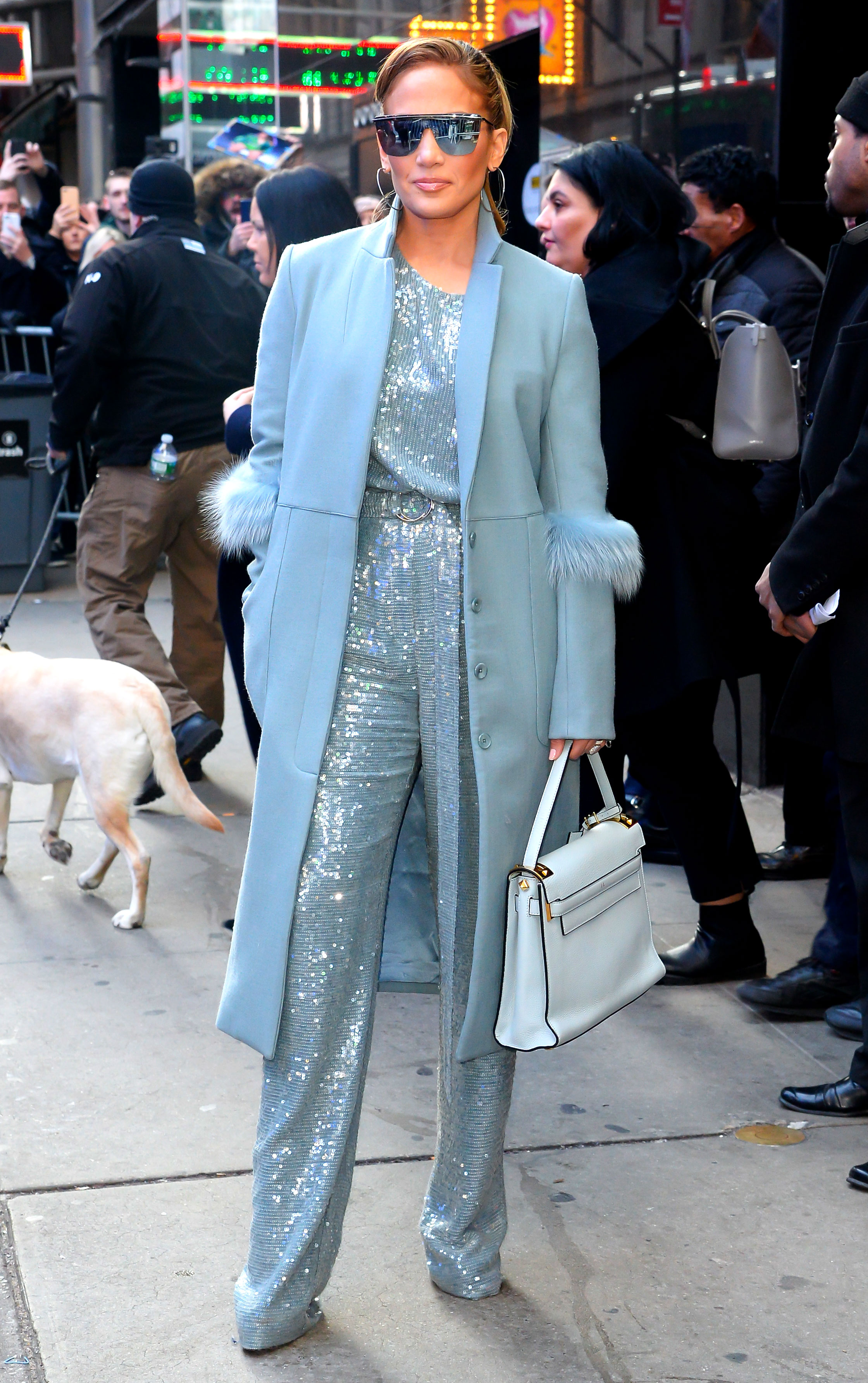 jennifer-lopez-Second-Act-press-sequin-jumpsuit-blue-coat - J. Lo brought some sparkle to Times Square for her appearance on Good Morning America on Wednesday, December 12, in a sequined Sally LaPointe two piece and fur-trimmed coat, metallic Jimmy Choo heels, a Valentino handbag and For Art's Sake sunglasses.