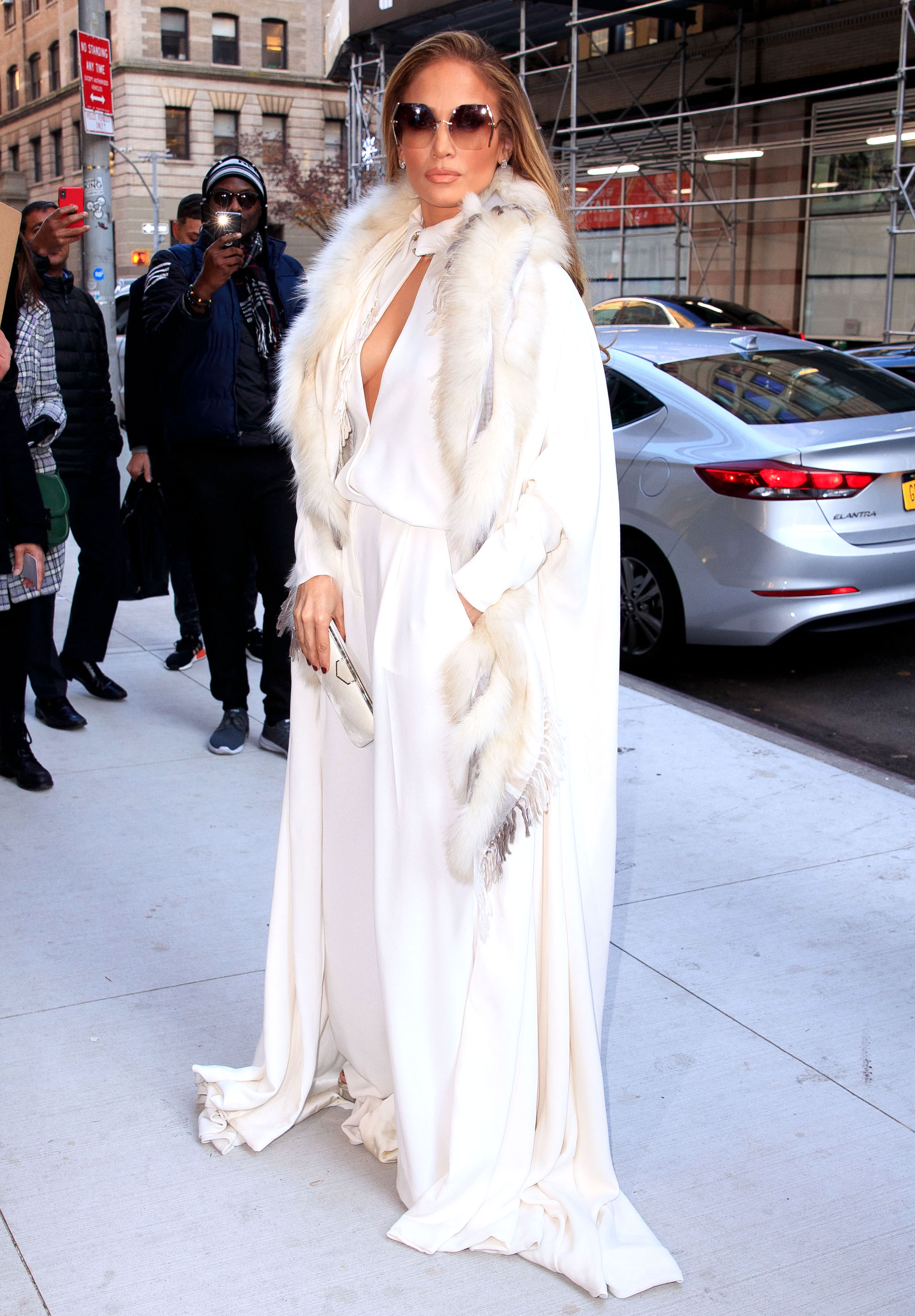 jennifer-lopez-Second-Act-white-dress - It doesn't get much chicer than all white everything, as she proved in a Stephane Rolland number that she paired with a fur stole, Jimmy Choo clutch and sandals and For Art's Sake shades on Tuesday, December 11.