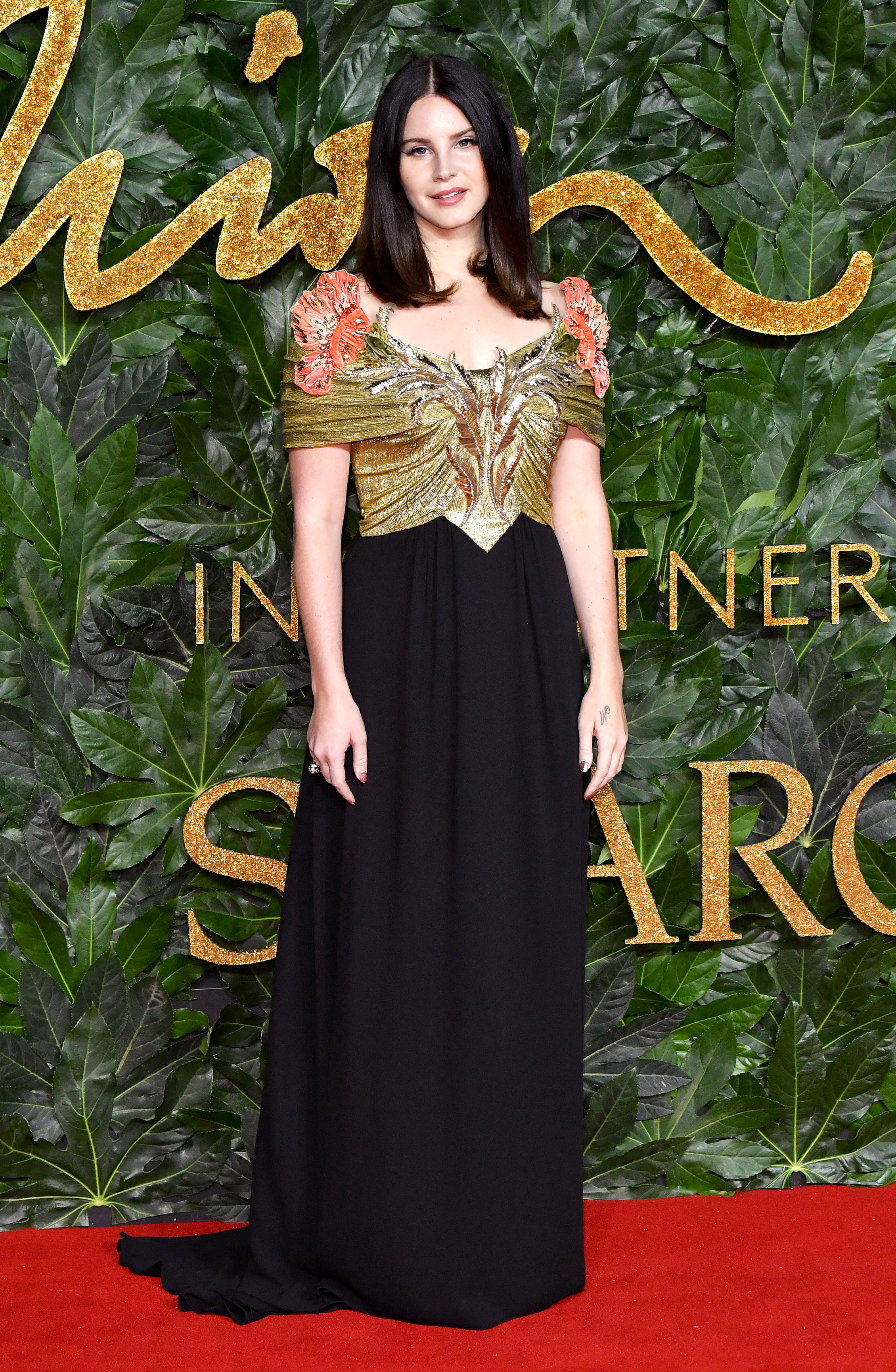 lana-del-rey - The Gucci ambassador sported a black and gold off-the-shoulder frock by the fashion house.