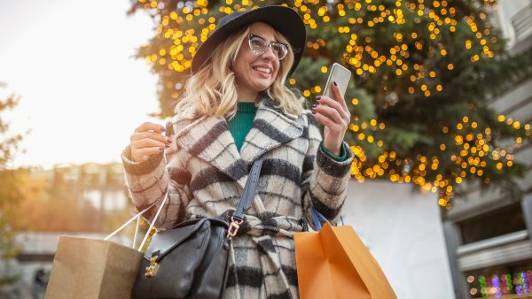 Carefree woman shopping downtown andusing mobile phone