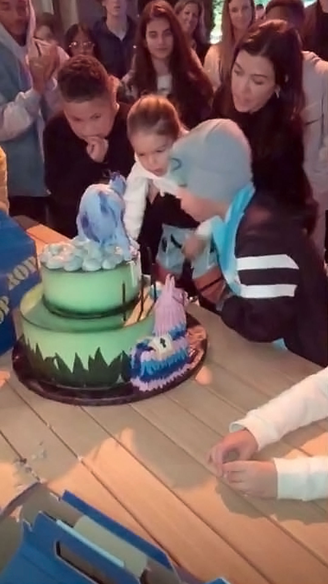 Kourtney Throws Sons a Fortnite-Themed Birthday Party - Kourtney held Reign as he helped Mason make a wish.