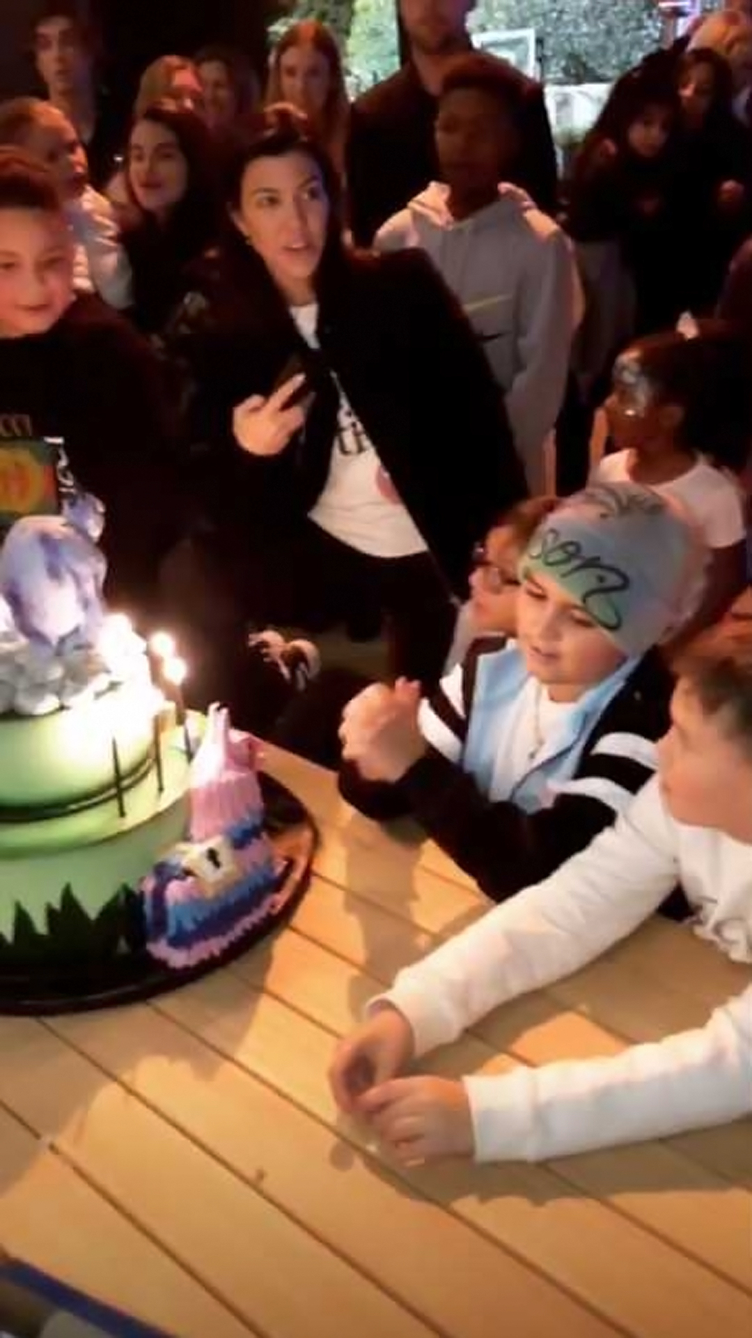 Kourtney Throws Sons a Fortnite-Themed Birthday Party - Kourtney smiled as Mason got ready to blow out the candles on his cake.