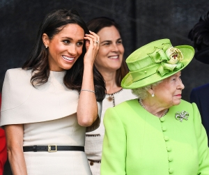 Queen Elizabeth II stands with Meghan, Duchess of Sussex accompanied by Samantha Cohen