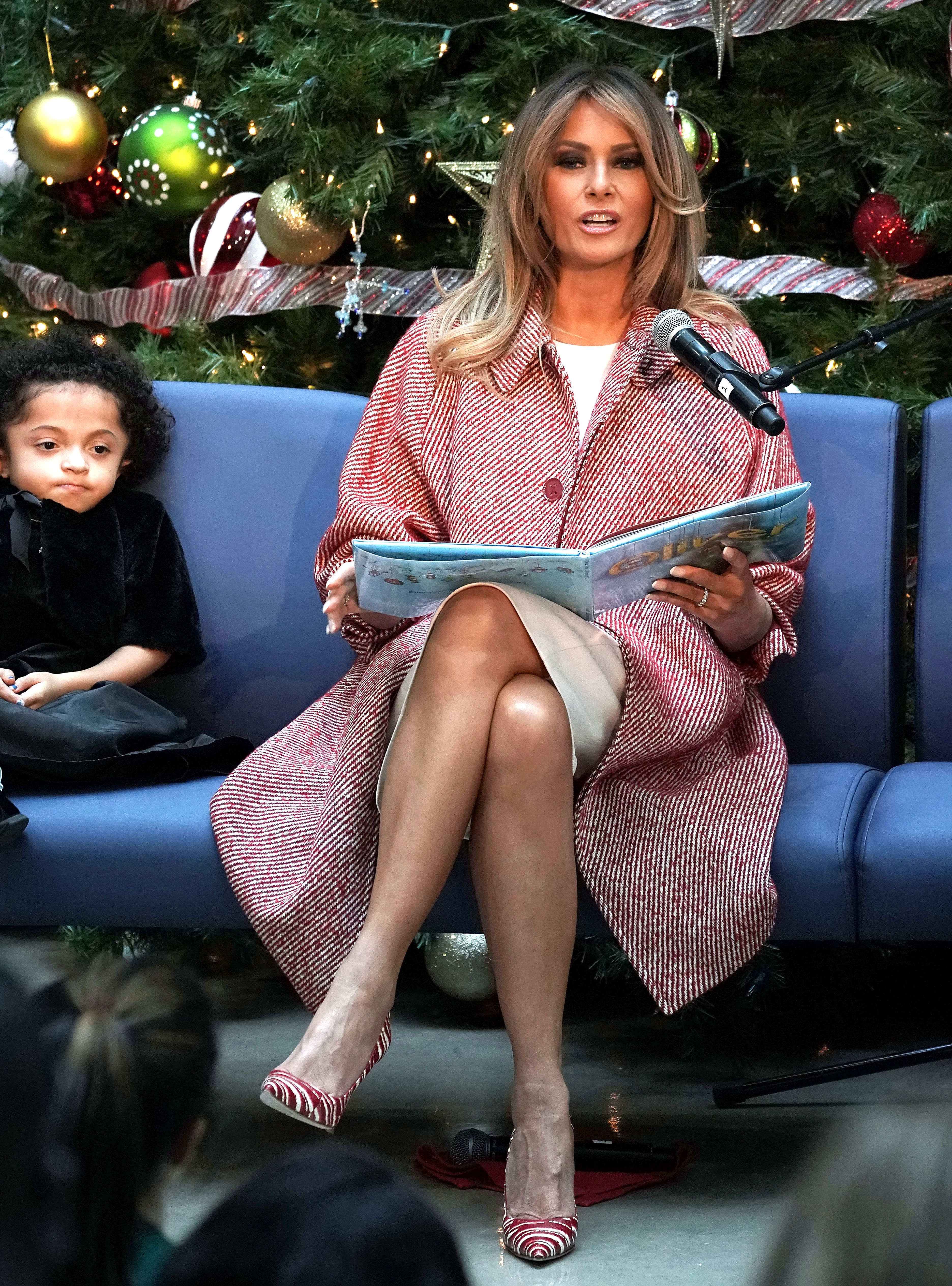melania-trump-striped-outfit-blonde-hair - Visiting the Children's National Hospital in Washington, D.C., the First Lady was festive in a $750 red and white Tomas Maier wool-blend coat that she paired with matching Manolo Blahnik heels and an ivory sheath dress.