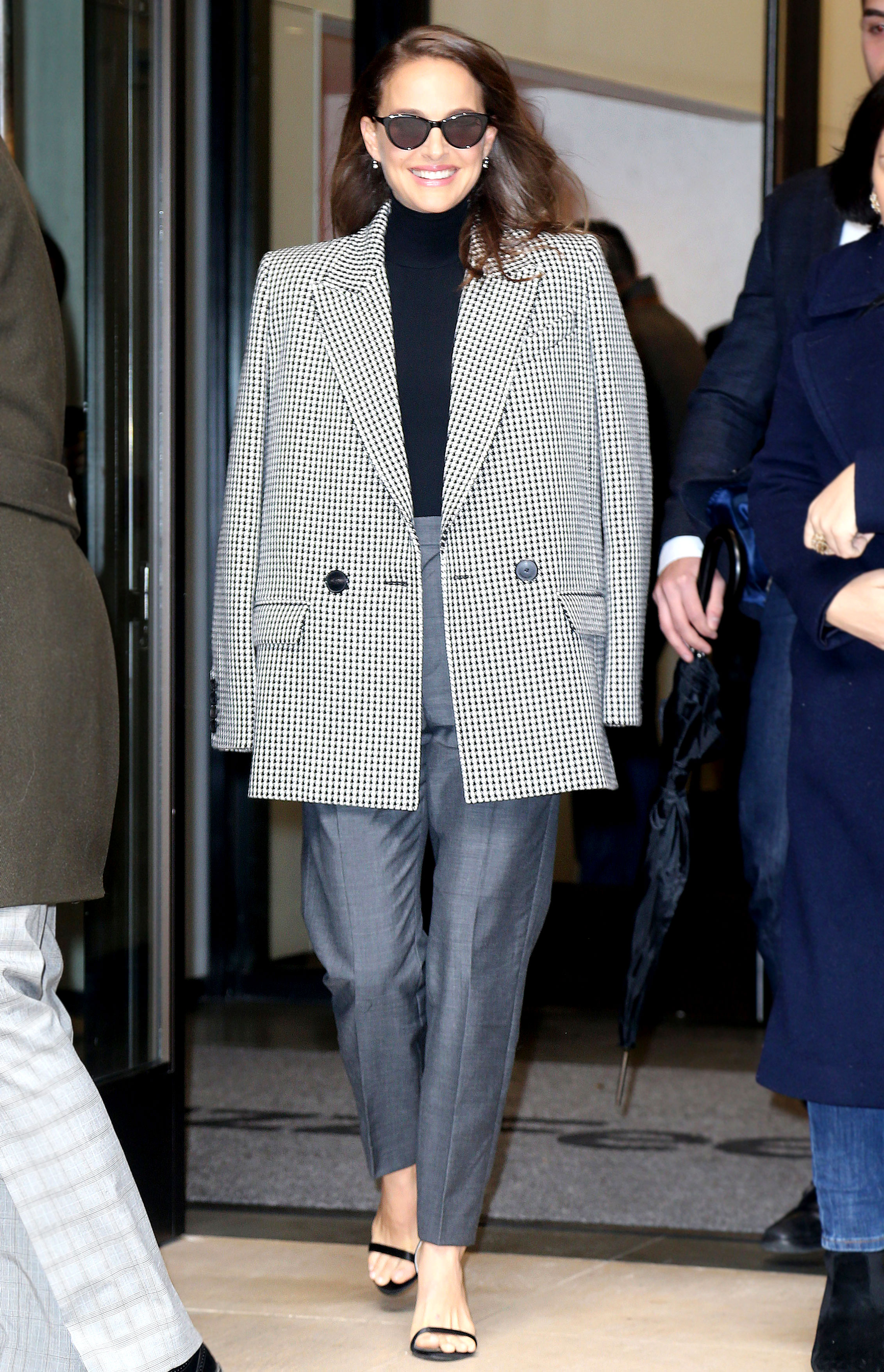 natalie-portman-gingham-coat - Out in NYC on Thursday, December 14, the Vox Lux star accessorized her chic Dior trousers and turtleneck combo with strappy sandals and a boxy herringbone blazer coat. The Oscar winner gets extra style points for chicly draping it over her shoulders.