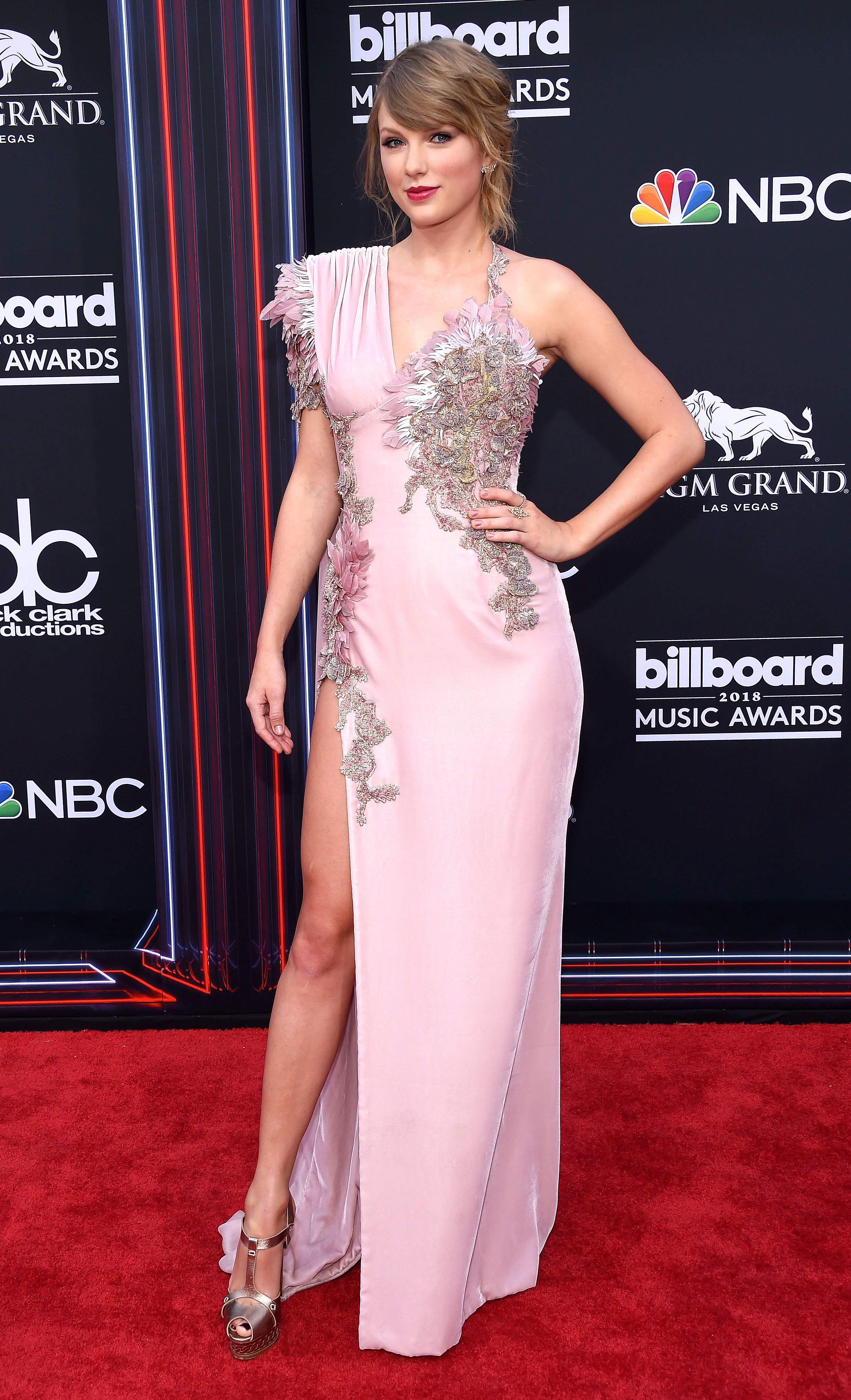 taylor-swift-billboard-pink-gown - At the 2018 Billboard Music Awards, the blonde beauty provided a bit of a #TBT in a single-shoulder, rose-colored velvet Atelier Versace gown embellished with sequined embroidery and feathers.
