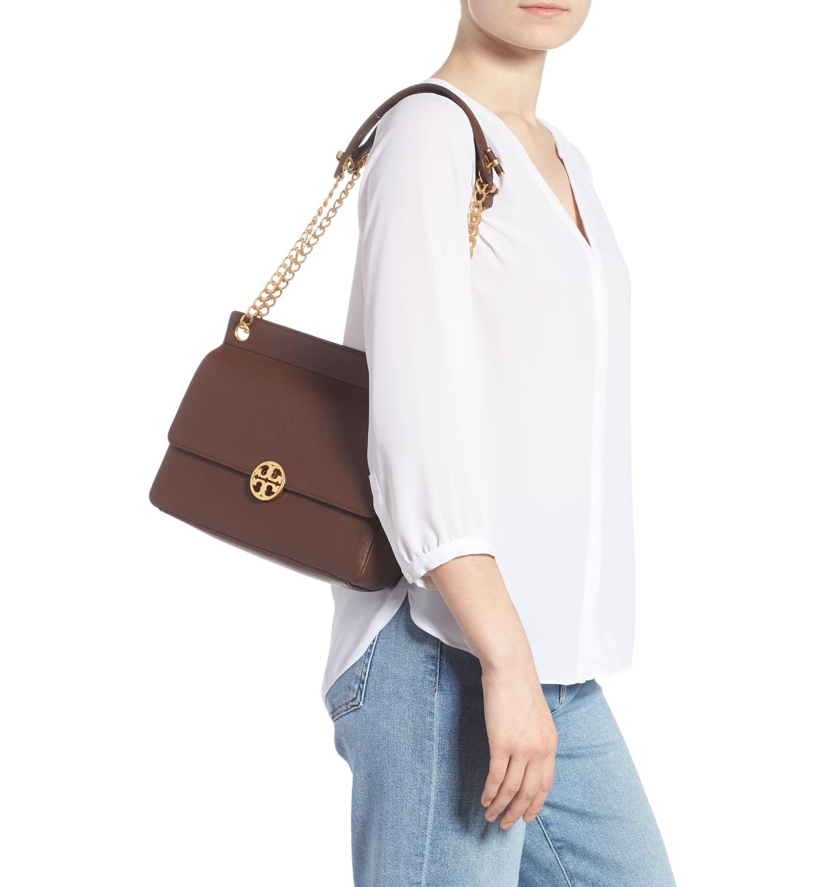 tory burch chelsea flap shoulder bag in brown on a model's shoulder
