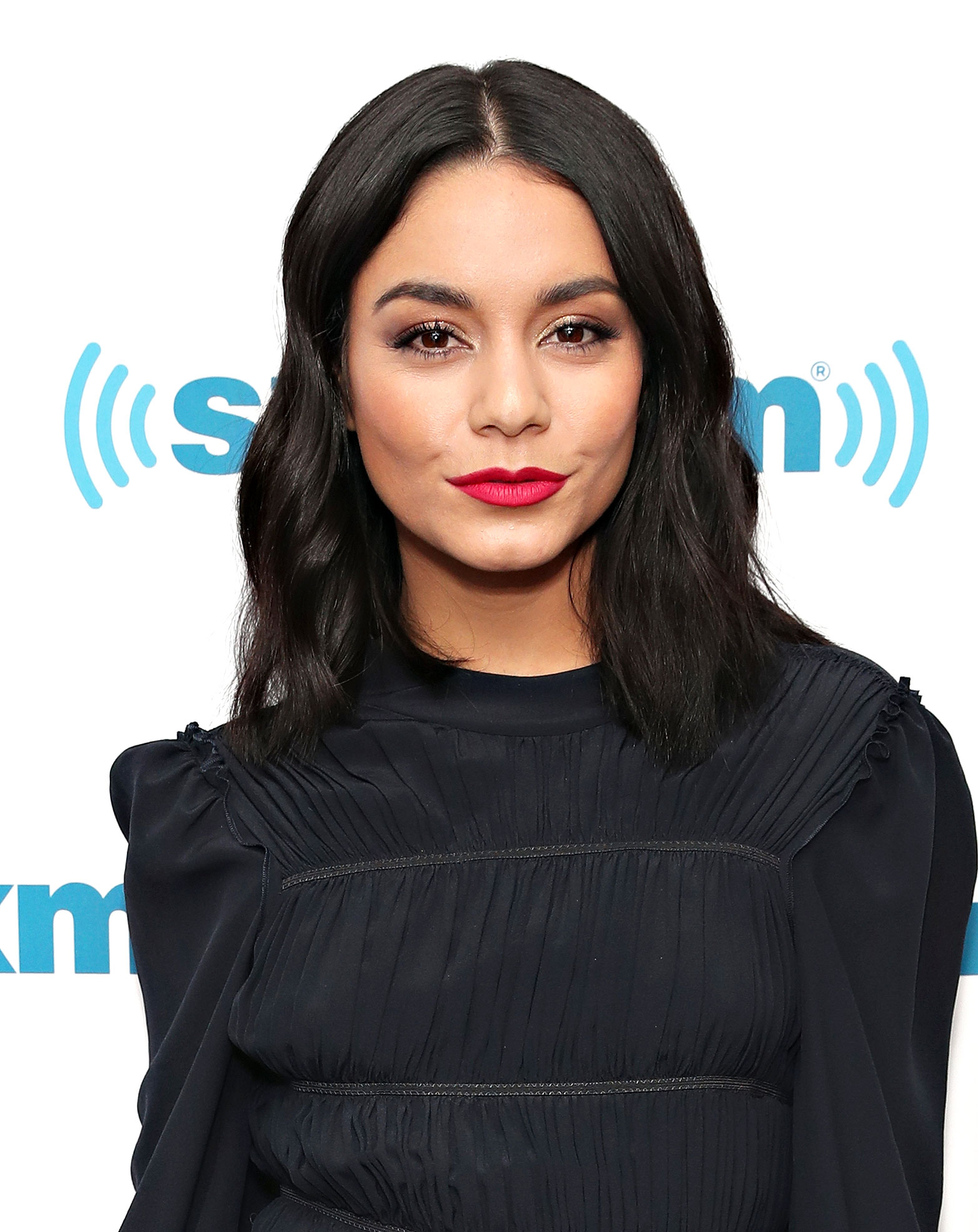vanessa-hudgens-red-lipstick - The best compliment to beautiful bronzy skin and a strong brown? A bold red lip, of course, as the Second Act actress rocked during a SirusXM interview on Wednesday, December 12.