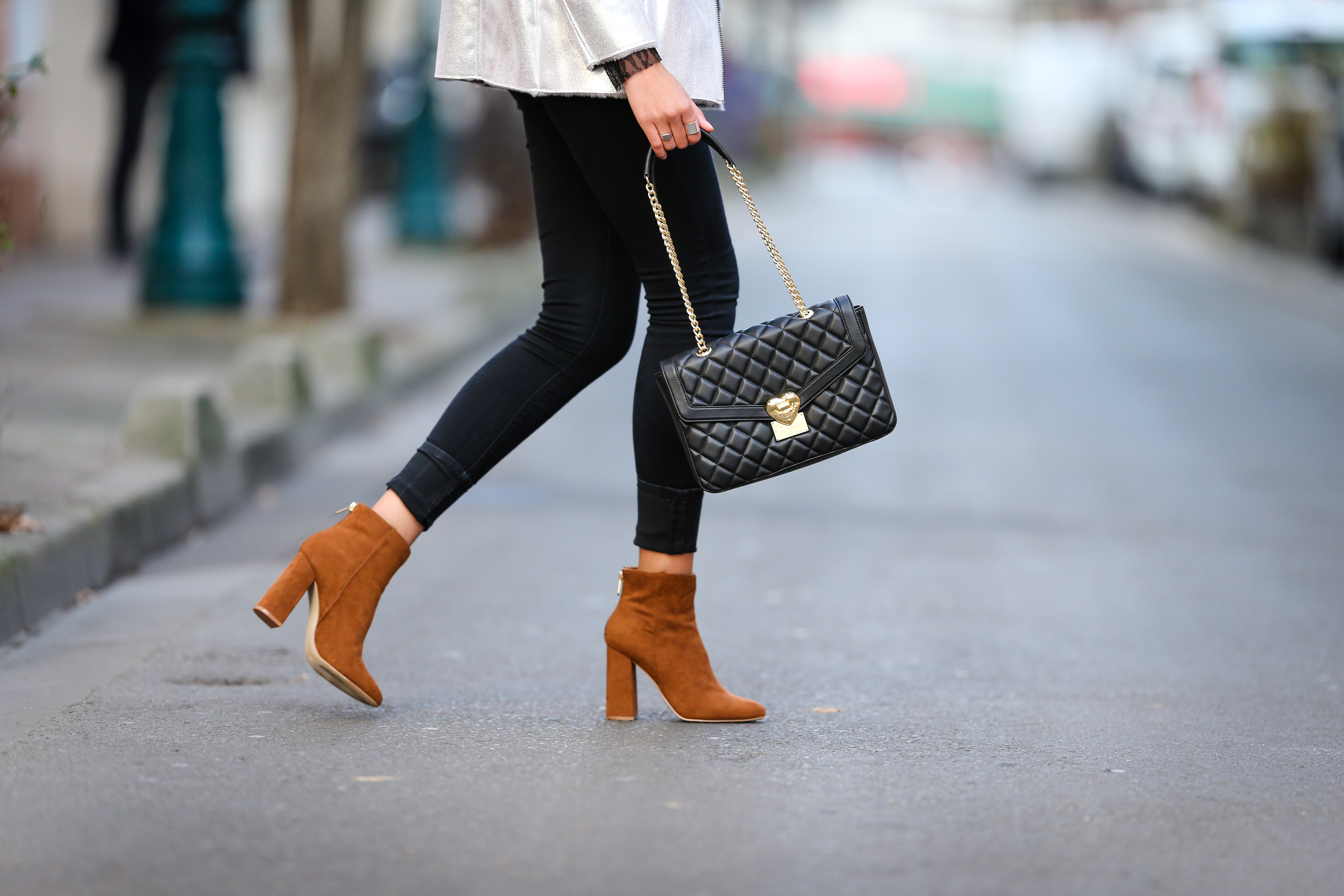 PARIS, FRANCE - DECEMBER 08: Syana Laniyan, fashion and life style blogger @syanafromparis, is wearing Just Fab brown suede shoes, an Asos silver coat with faux fur, an Asos black top with lace, Asos black pants, and a Moschino black bag, on December 8, 2016 in Paris, France. (Photo by Edward Berthelot/Getty Images)