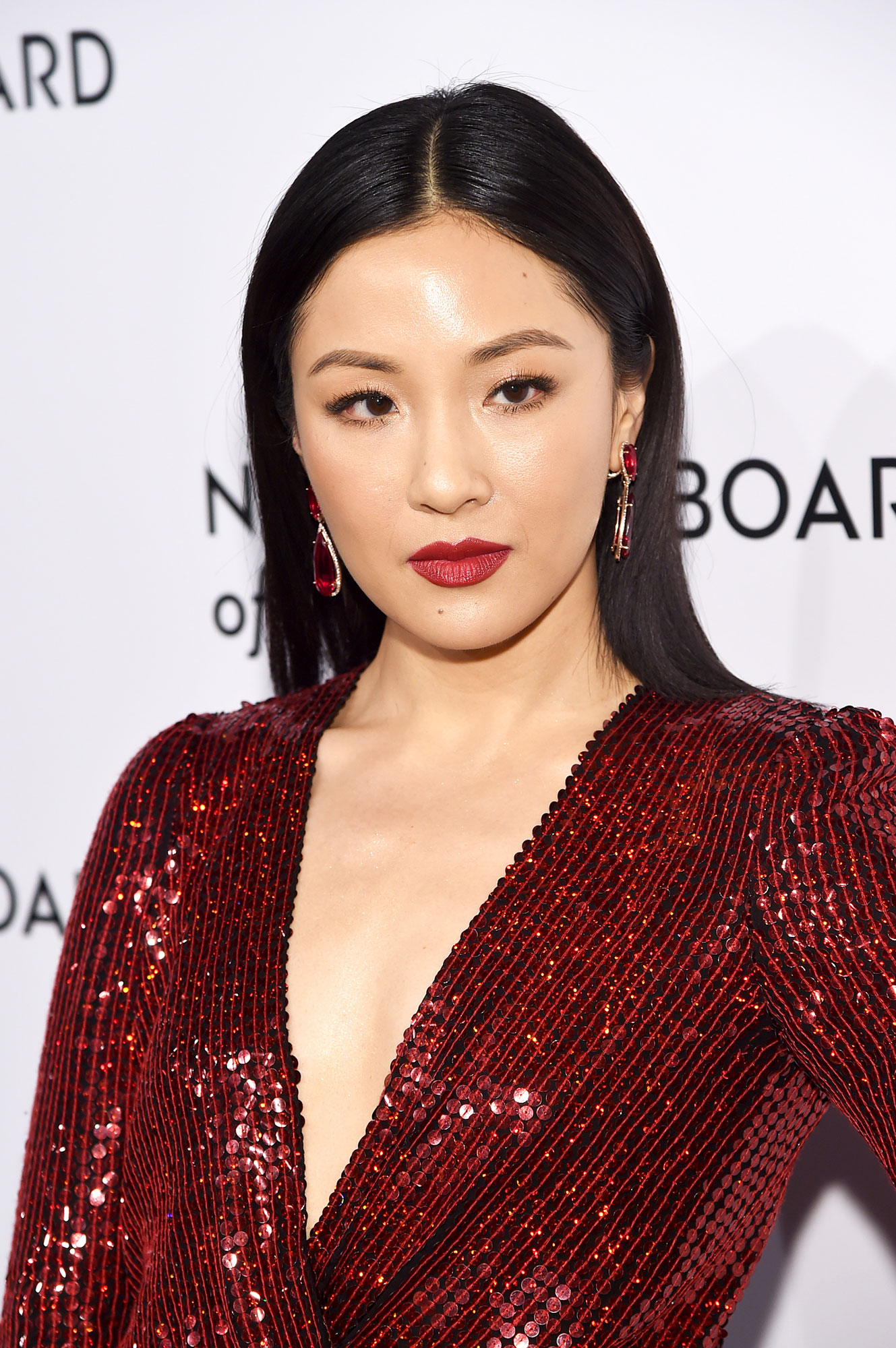 Constance Wu - Matching her lip shade to her sequined dress and eye-catching jeweled earrings, the star of Crazy Rich Asians wore a seductive cardinal red to the National Board of Review Gala on January 8.