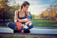 Runner girl is resting and checking her arm band in the park