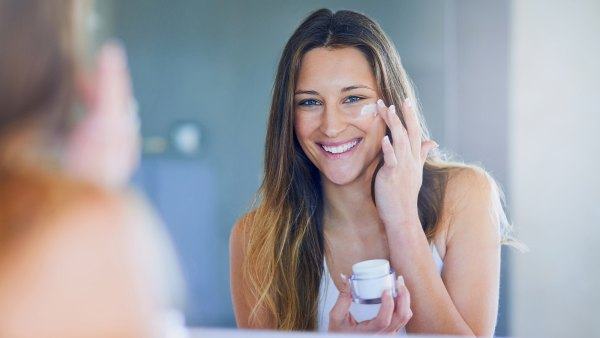 Portrait of a beautiful young woman applying moisturizer to her face while looking in the mirror