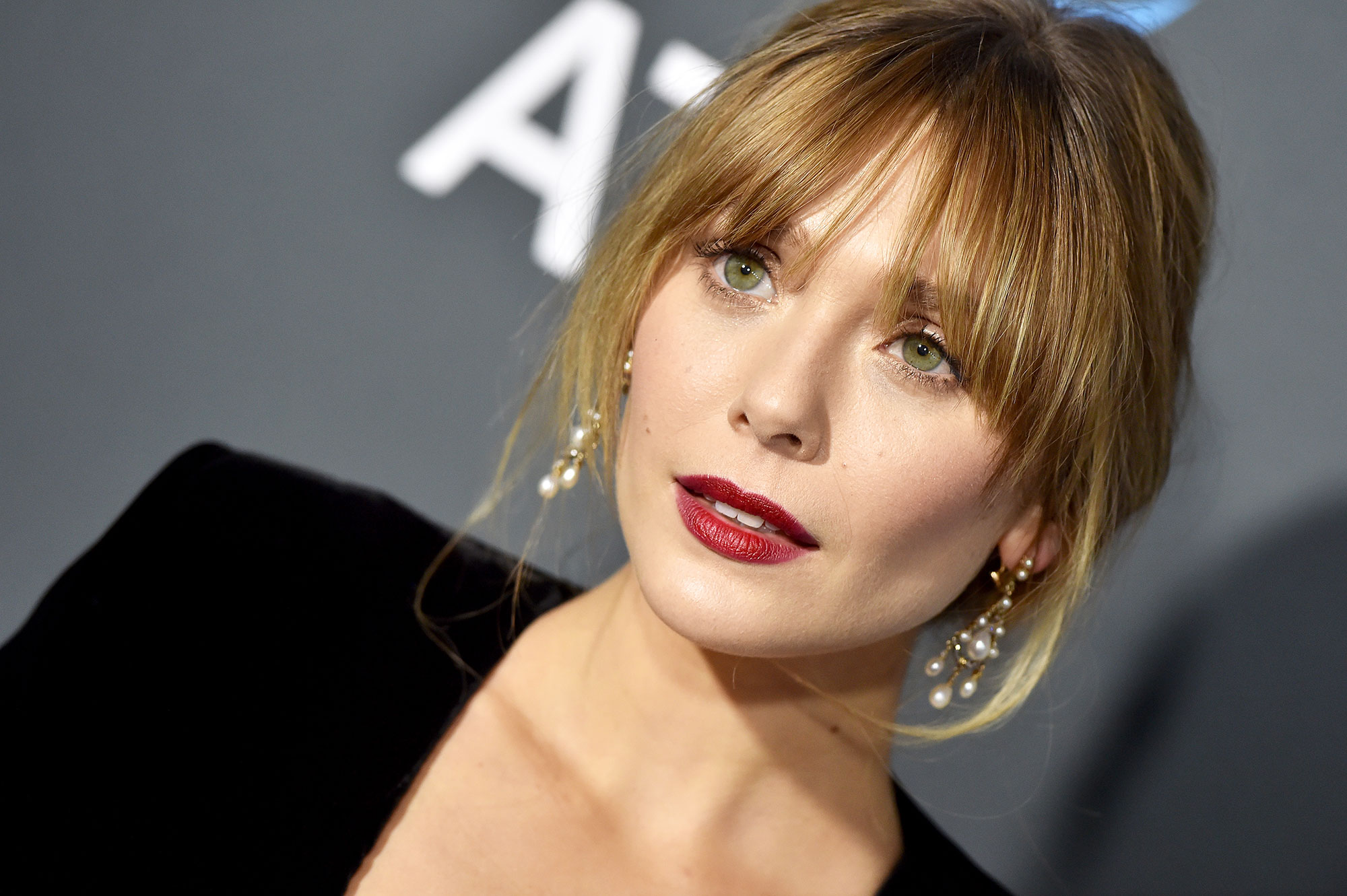 Elizabeth Olsen Critics' Choice Awards 2019 - With sultry curtain bangs by mane man Mark Townsend using Dove products and a modern nude eye and brick red lips courtesy of makeup artist Pati Dubroff using Chanel.