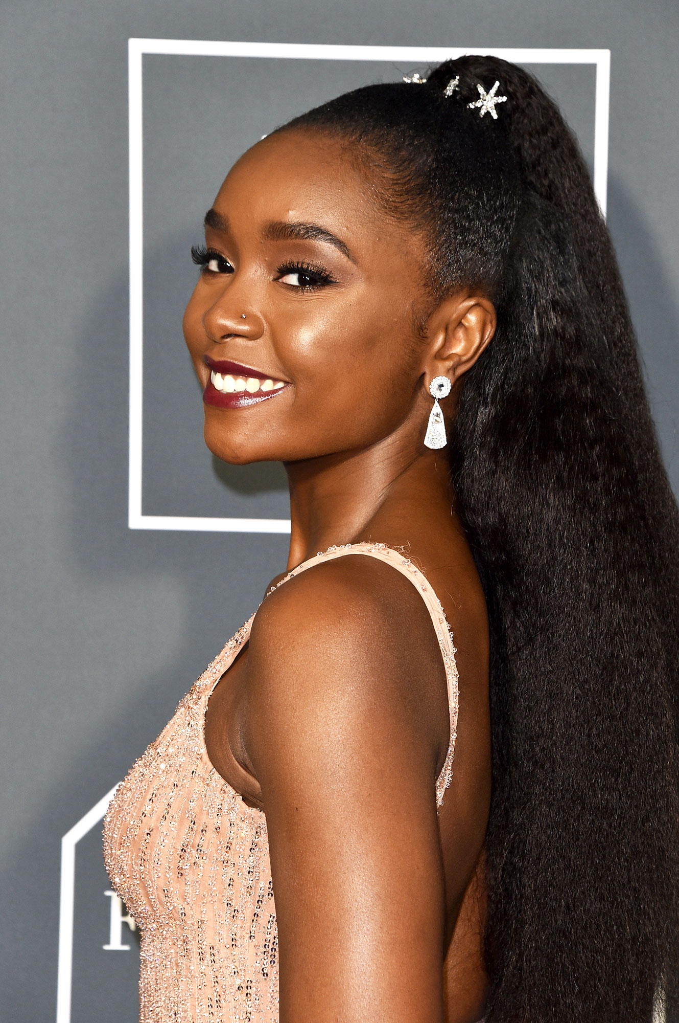 Kiki Layne Critics' Choice Awards 2019 - With an embellished half up bun using Jennifer Behr pins by mane maven Lacy Redway and smokey eyes, bold brows and burgundy glossy lips.