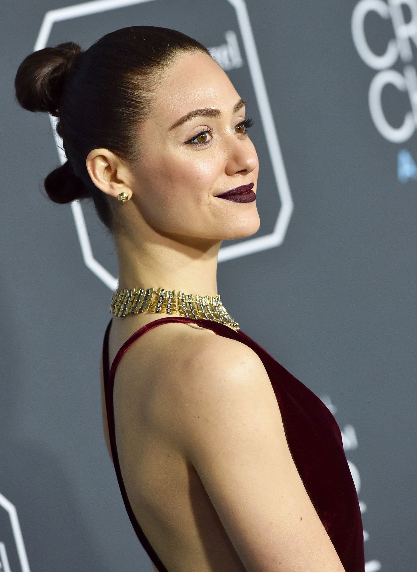 Emmy Rossum Critics' Choice Awards 2019 - With a sculpted chignon with double buns by hairstylist Giannandrea and retro black cherry lips by makeup pro Jo Baker.