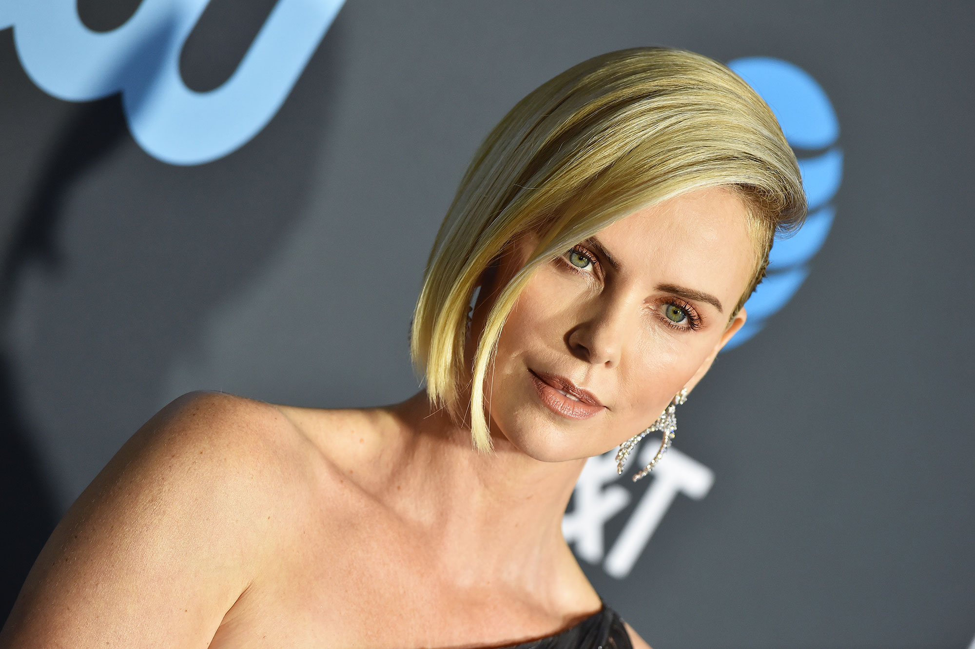 Charlize Theron Critics' Choice Awards 2019 - With a sideswept intricataly woven updo and gilded bar embellishment by hair pro Adir Abergel using Virtue Labs products and bronzed apricot makeup by Kate Lee using Chanel.
