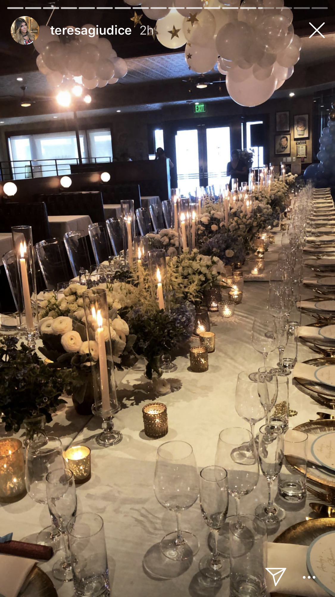 andy cohen, baby shower - The Palm restaurant in L.A. was filled with white balloons while the very long table was set with gold-edged plates and several beautiful floral centerpieces.
