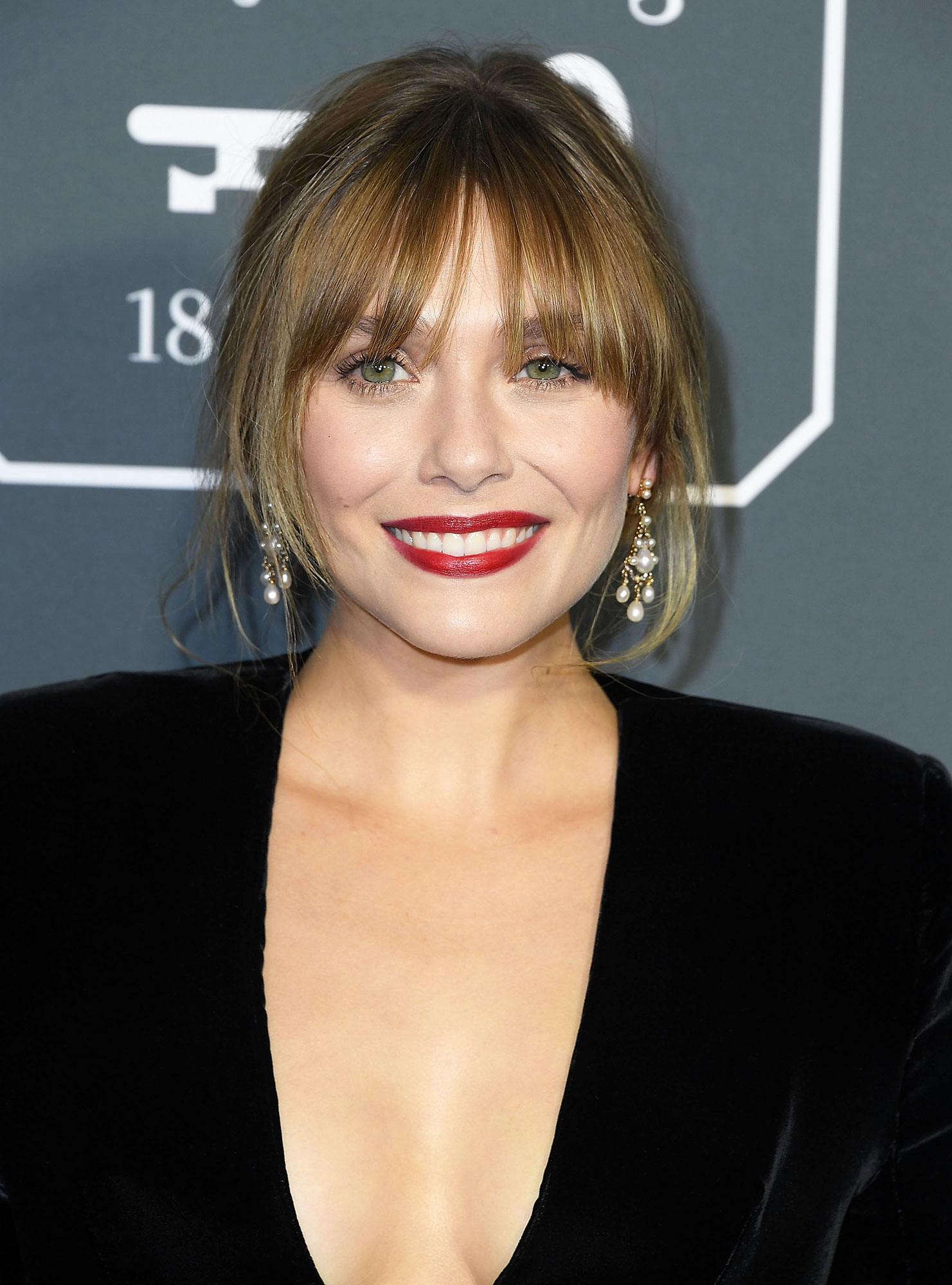 Elizabeth Olsen Celebrity Bangs: Fierce Fringe Inspo For Your Next Haircut - Eyelash-length wispies made the perfect complement to the actress' updo at the 2019 Critics' Choice Awards.