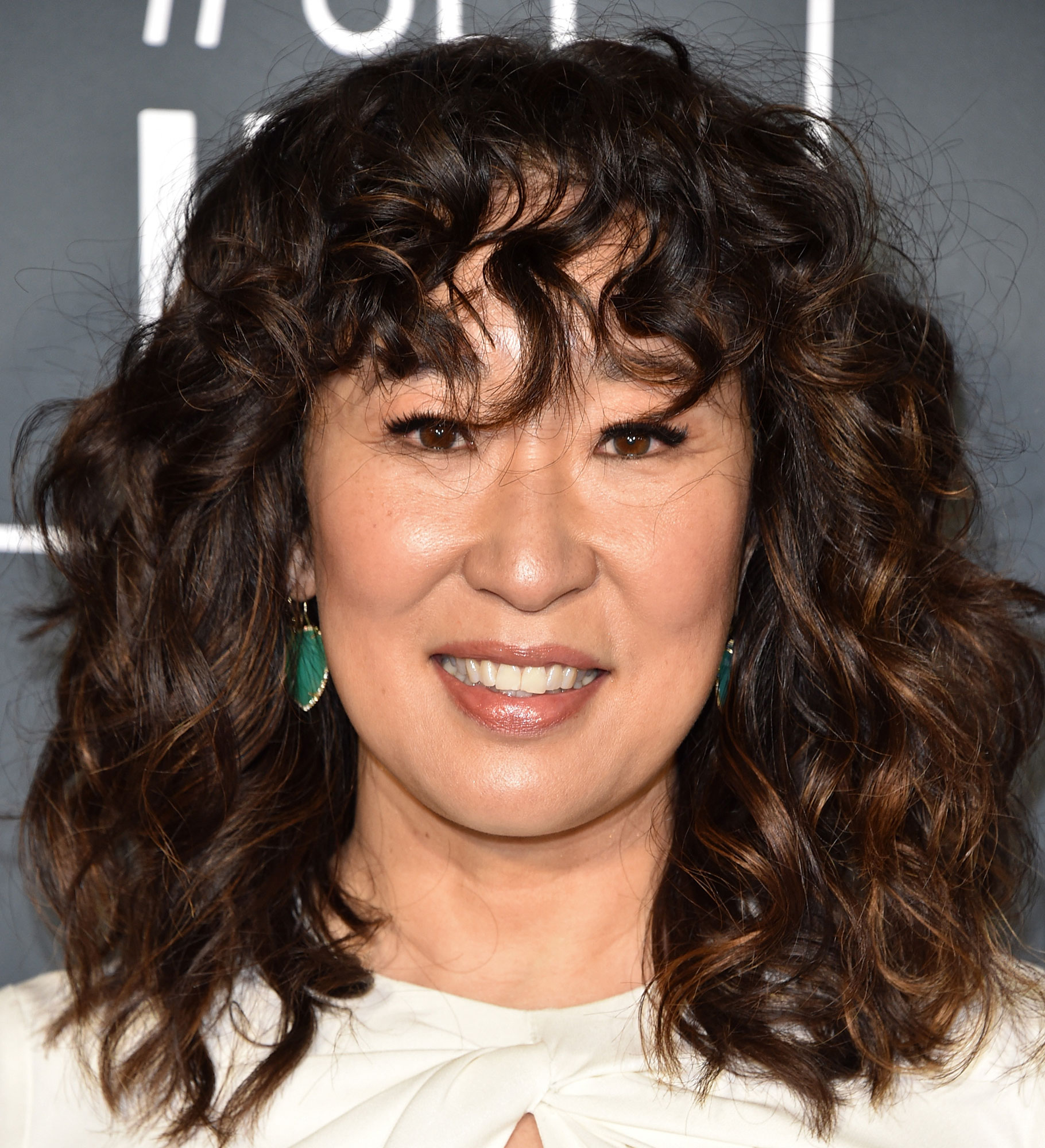 """Sandra Oh Celebrity Bangs: Fierce Fringe Inspo For Your Next Haircut - While curly hair and bangs may sound like a terrifying combo, celeb hairstylist Ted Gibson cut fresh fringe for the Killing Eve star just before the 2019 Critics' Choice Awards. """"Those with curly hair need a bit of softness and bangs need to be broken up a bit,"""" he tells Us ."""