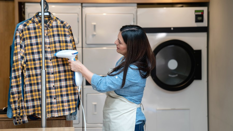 Woman working at a laundry service using a garmet steamer on shirt - Business industry concepts