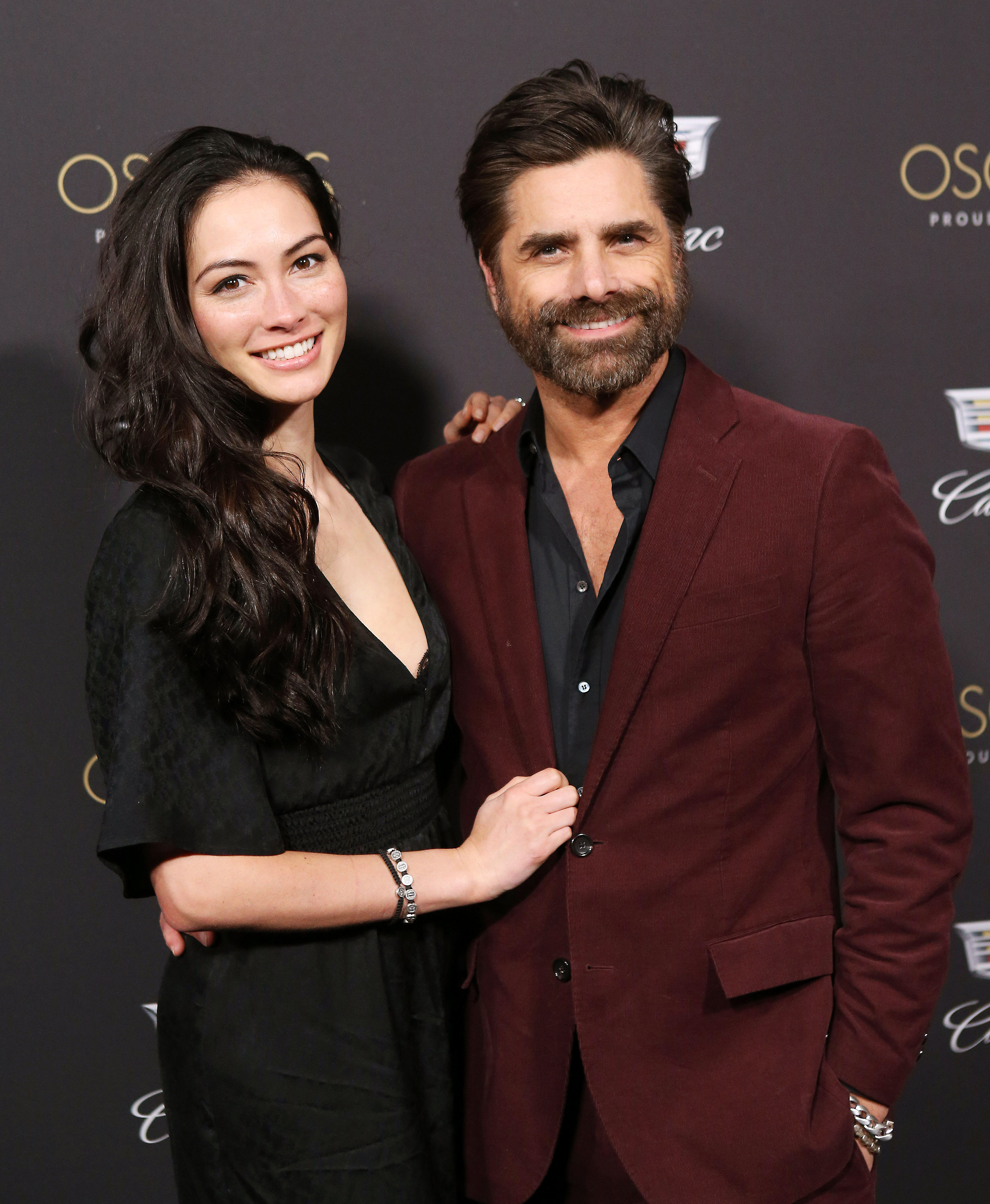 """John Stamos and Caitlyn McHugh Cadillac - The Full House alum, who celebrated the impending ceremony with wife Caitlin McHugh , has come a long way since his past Oscars traditions. """"We'd sit in front of the TV and eat Chinese food and watch the show,"""" Stamos, 55, told Us and other reporters at Cadillac's Fourth Annual Oscars Cocktail Party."""
