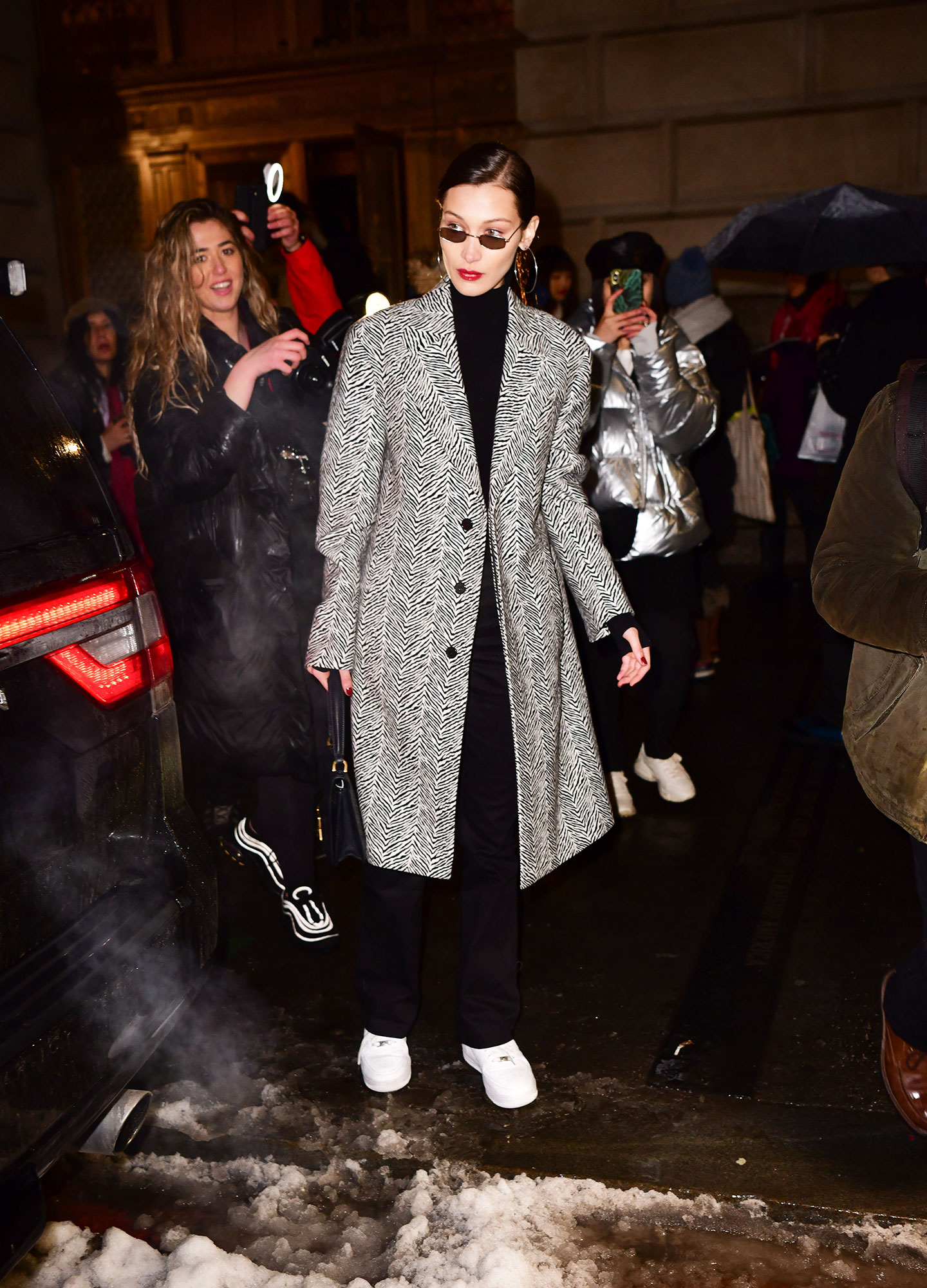 Bella Hadid - Defining model-off-duty, the youngest Hadid sister was seen leaving the Oscar de le Renta show on February 12 in a turtleneck and black and white jacket she paired with tiny shades and white sneakers.